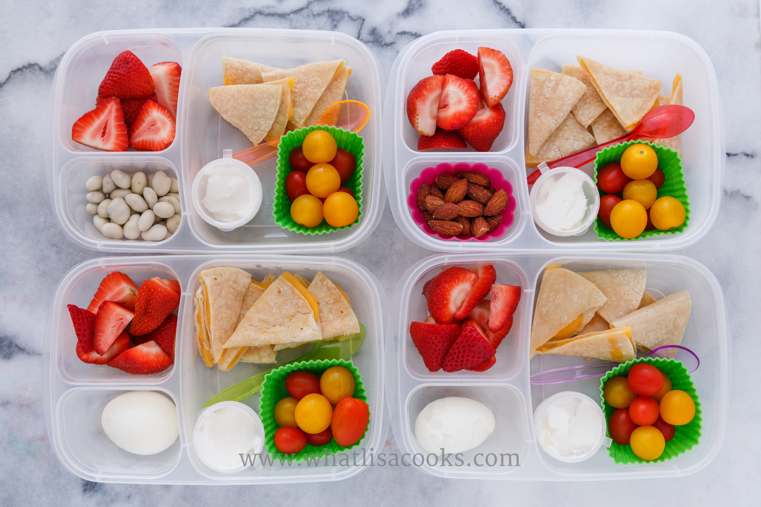 Quesadillas on gluten free corn tortillas, tomatoes, sour cream, strawberries.  Two have a boiled egg, one has almonds, one has yogurt covered raisins.  Packed in EasyLunchboxes, with  silicon muffin cups  and these  dip cups .