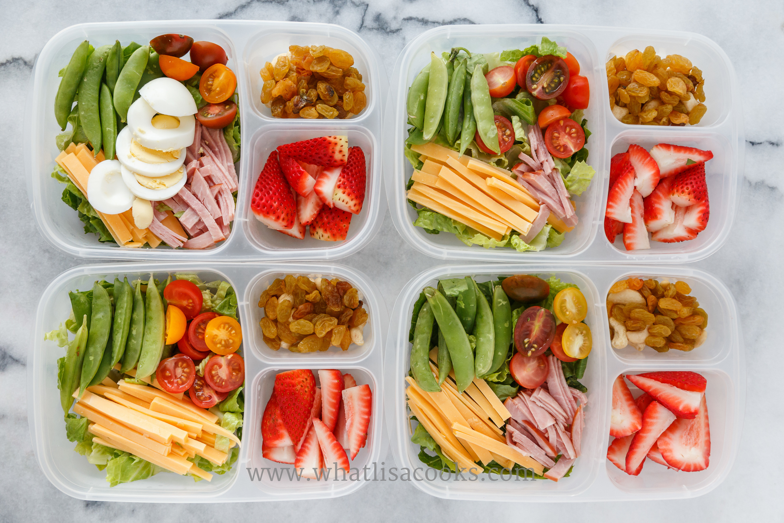 """Don't call it salad"".  My kids say they don't like salad, but they like all of this stuff!  Lettuce, tomatoes, cheddar cheese, ham, and sugar snap peas. One has sliced boiled egg. On the side: strawberries, raisins, and cashews. Packed in  Easy Lunchboxes ."