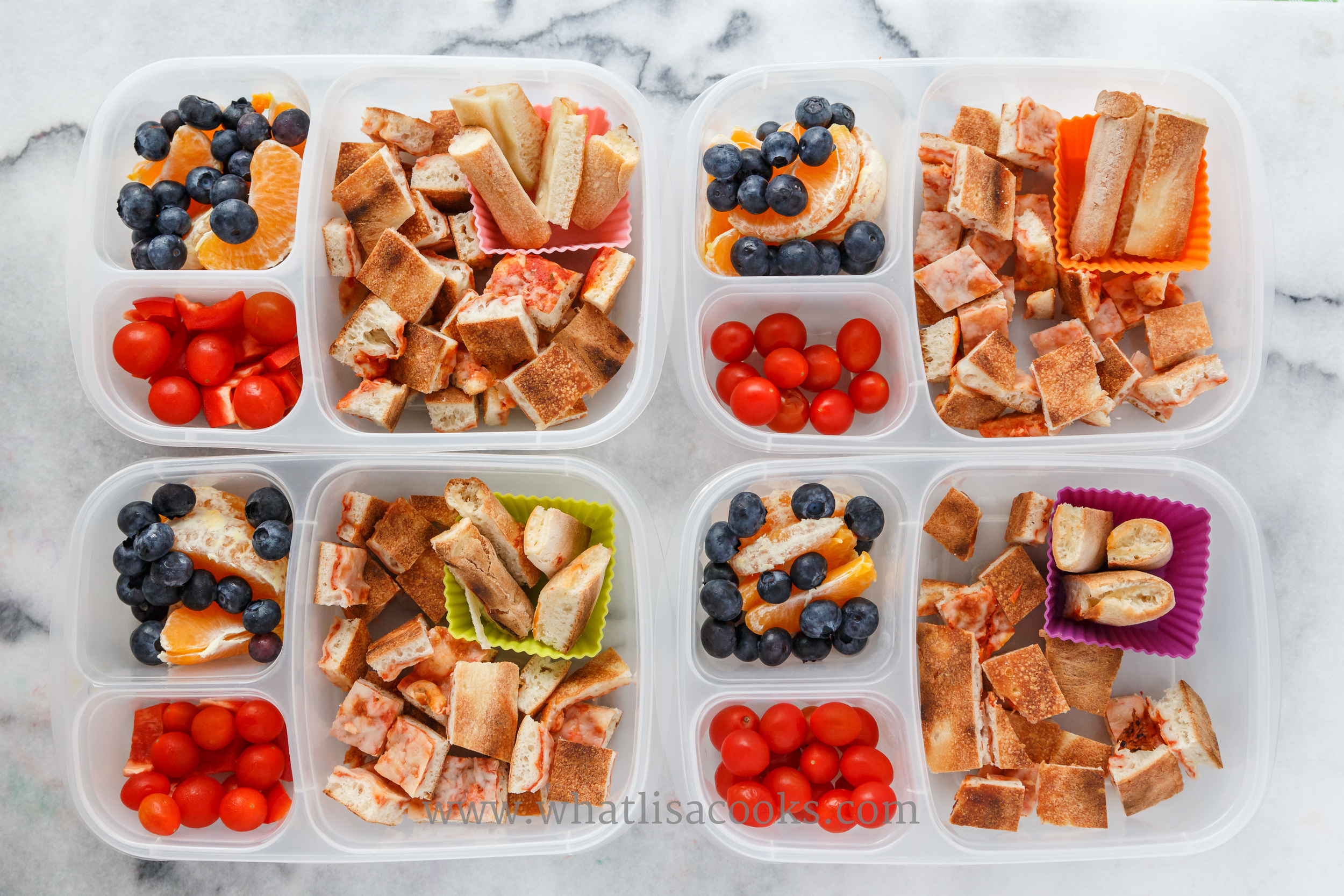Leftover pizza cut in bites for easier and faster eating, with oranges, blueberries, and tomatoes.  Packed in  Easy Lunchboxes .