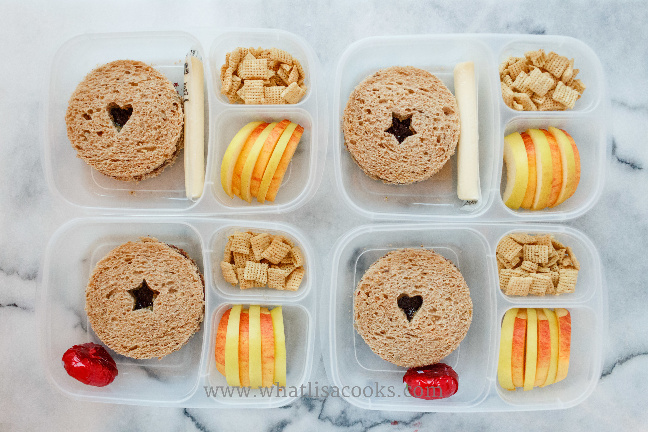 Sunbutter & jam sandwiches, cut in a circle with a little shape in the center.  A simple way to make lunch more fun.  With cheese, chex and apples on the side.  Two different apples, sliced and alternated.  The sandwich is cut with a  round biscuit cutter , and the shapes with some  mini cookie cutters .