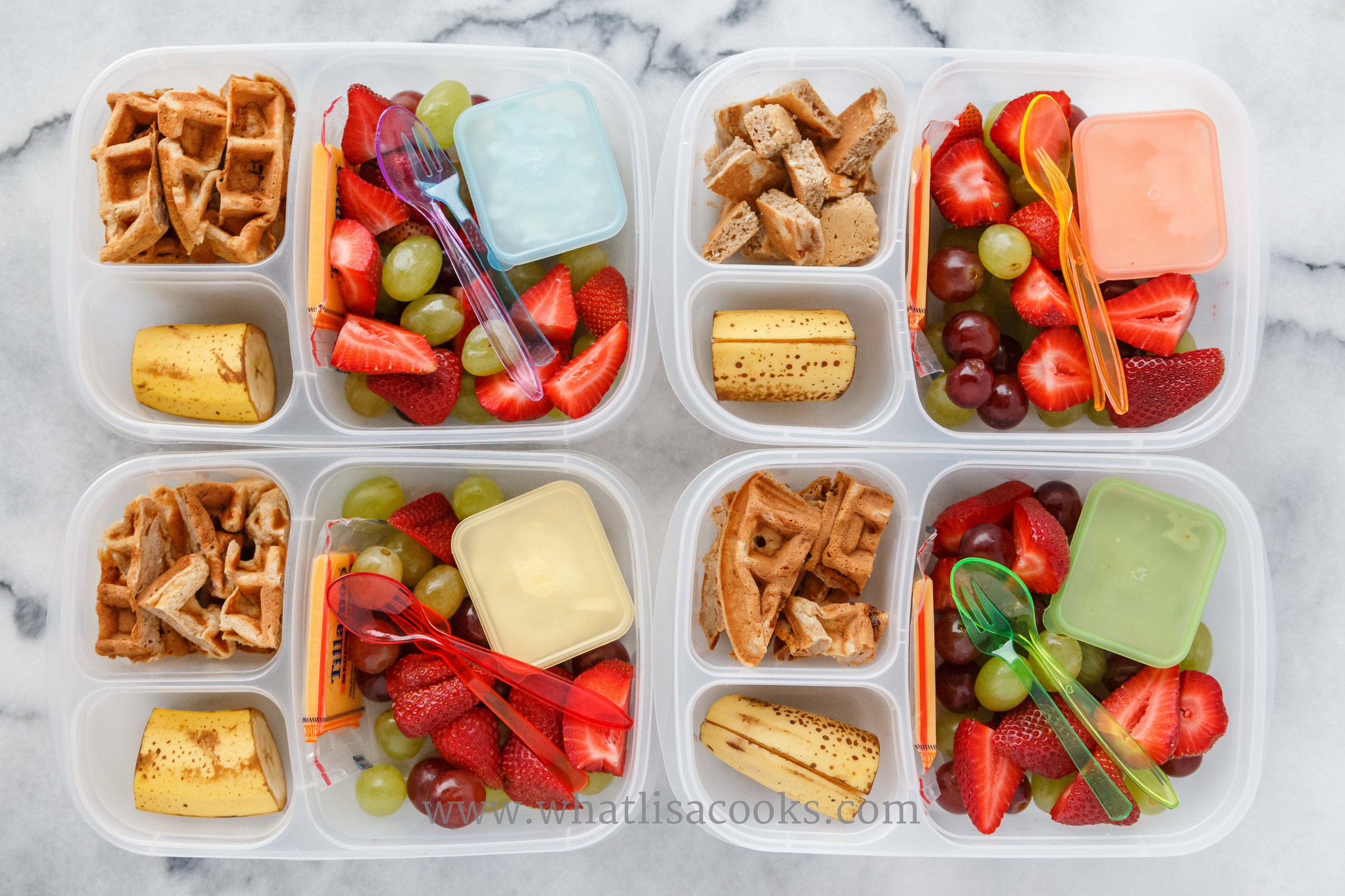 Waffle bites, banana, strawberries, grapes, and cheese.  One has whipped cream for dipping, one has cottage cheese, two have yogurt. Packed in  Easy Lunchboxes .