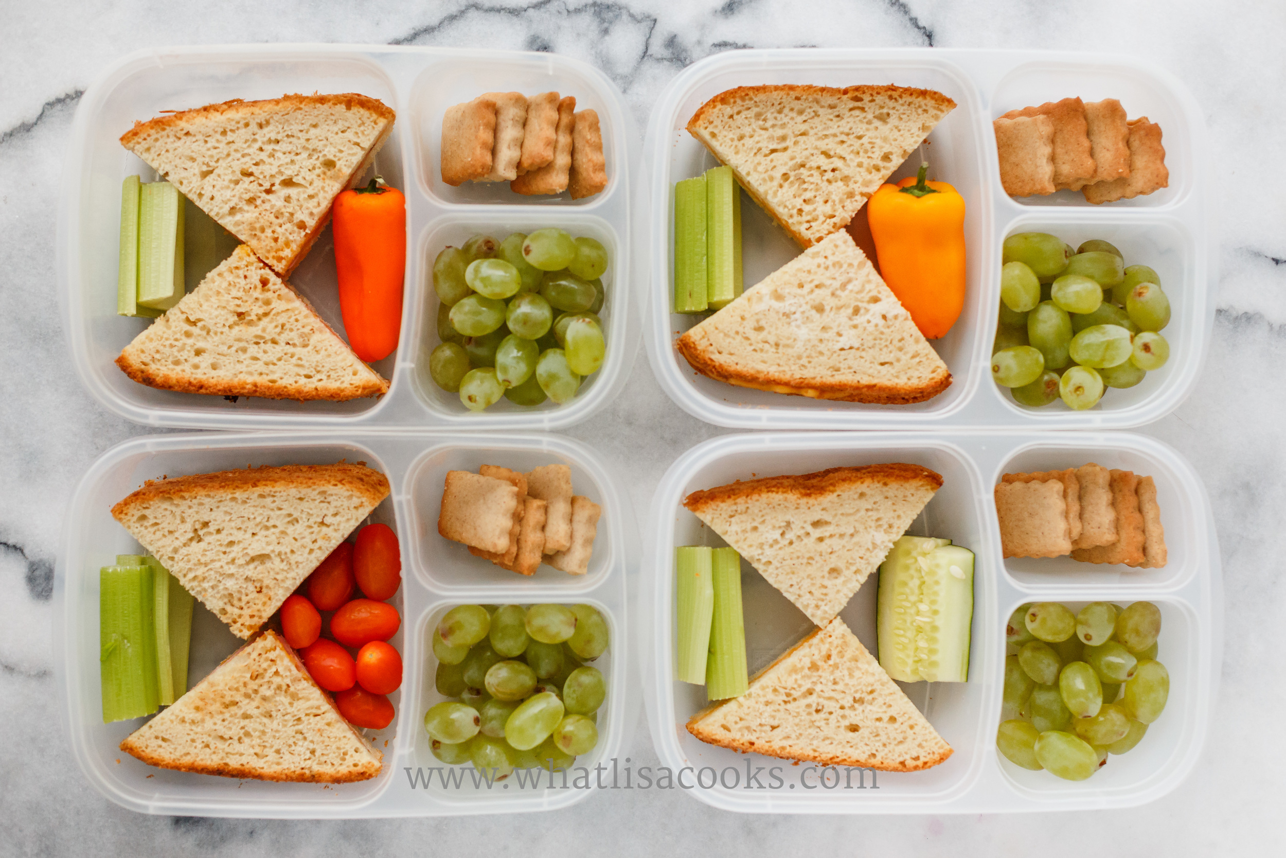 Toasted cheese sandwiches on homemade bread, veggies, grapes, and sugar cookies.  Packed in  EasyLunchboxes .