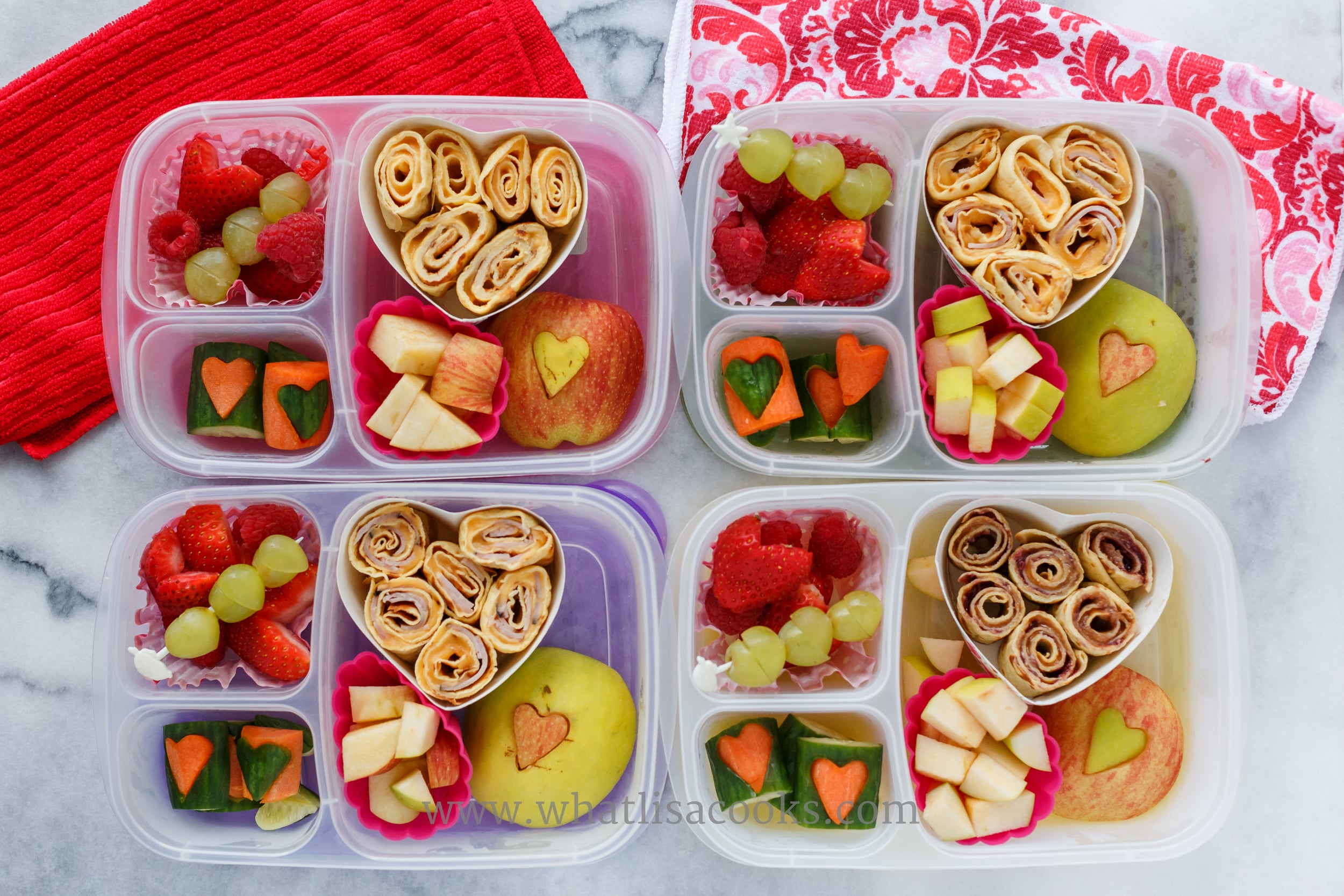 Crepe rolls with cheese and ham, apples with heart cutouts, carrots and cucumbers with heart cutouts, grapes and strawberries.