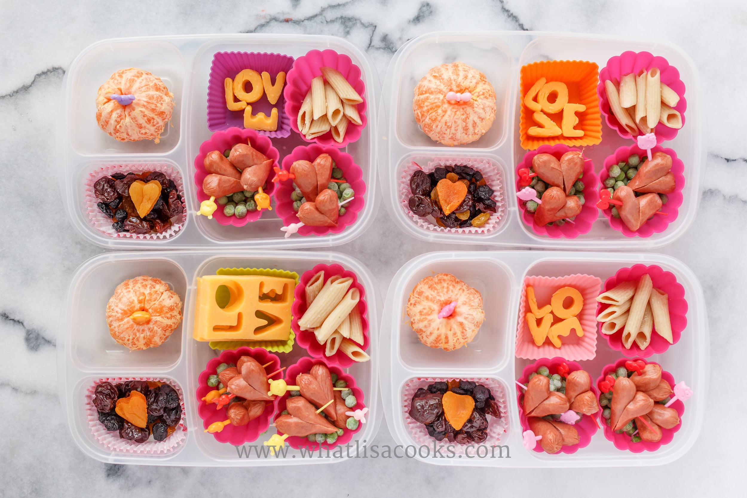 Thick slices of cheese with LOVE cut out with mini letter cutters, pasta, hot dog hearts, peas, dried fruit mix with a dried apricot heart.