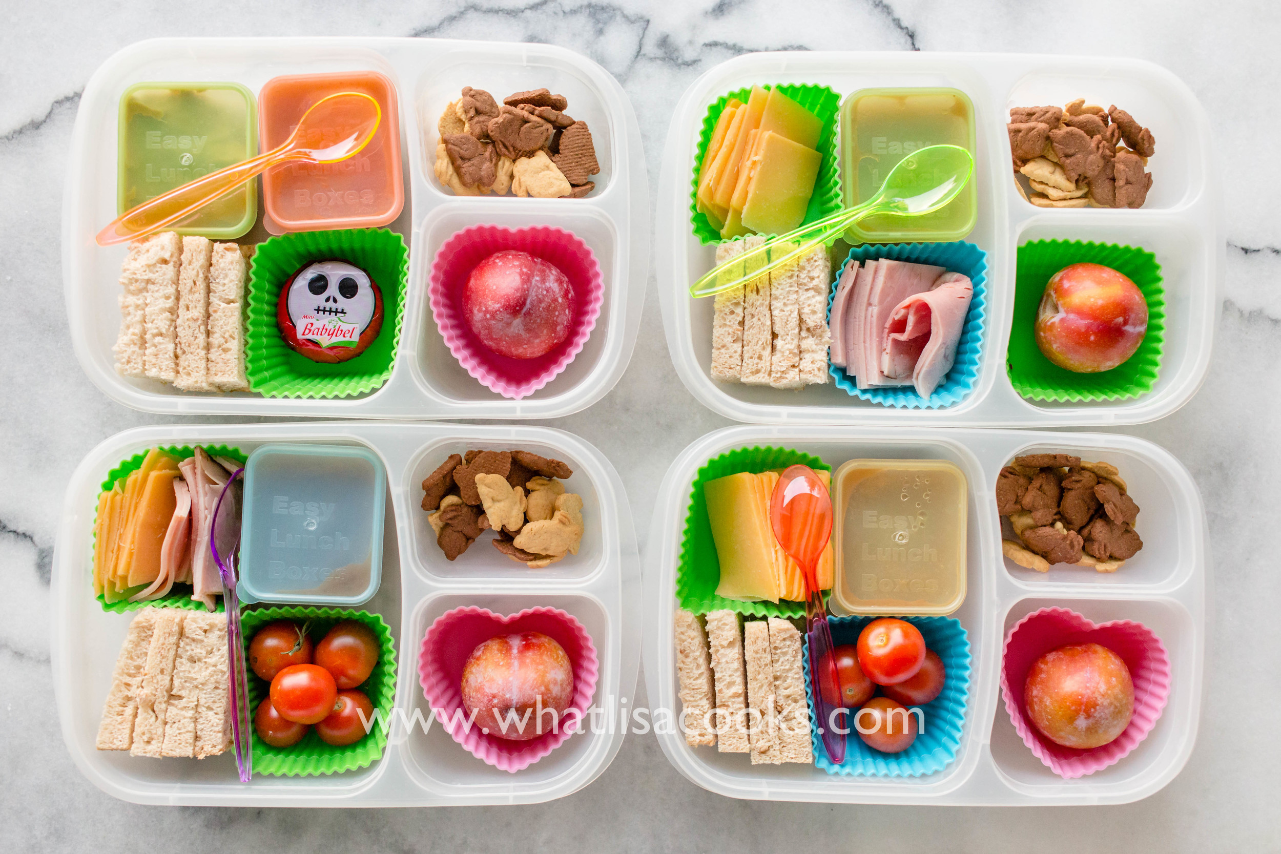 Make your won sandwich kit, with bread, cheese, ham, and one has peanut butter. Applesauce, tomatoes, cookies, and a plum on the side.