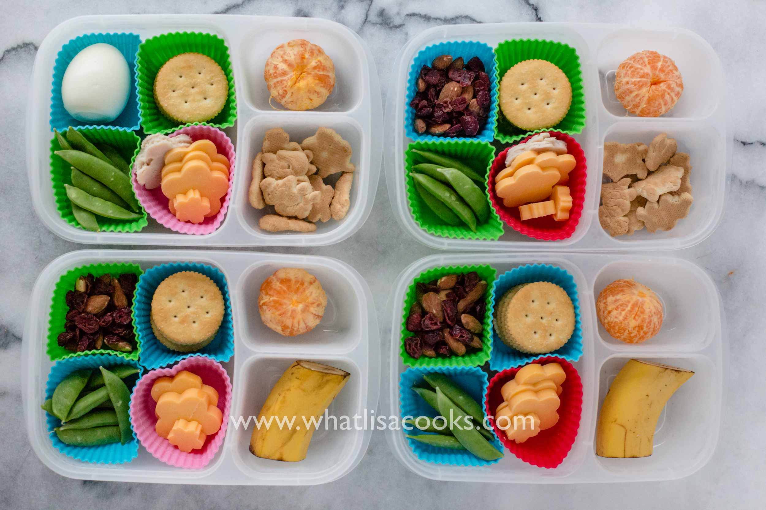 Crackers, cheese, turkey, dried fruit, sugar snap peas, orange, banana, and one has a boiled egg.