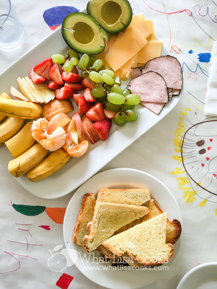 A more generous platter for a midday brunch/snack - fruit, cheese, ham, toast.