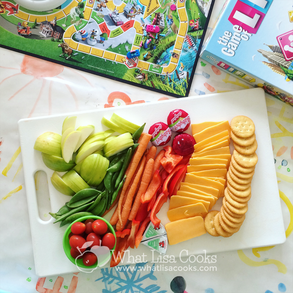 A cutting board filled with fruit, veggies, cheese, and crackers.
