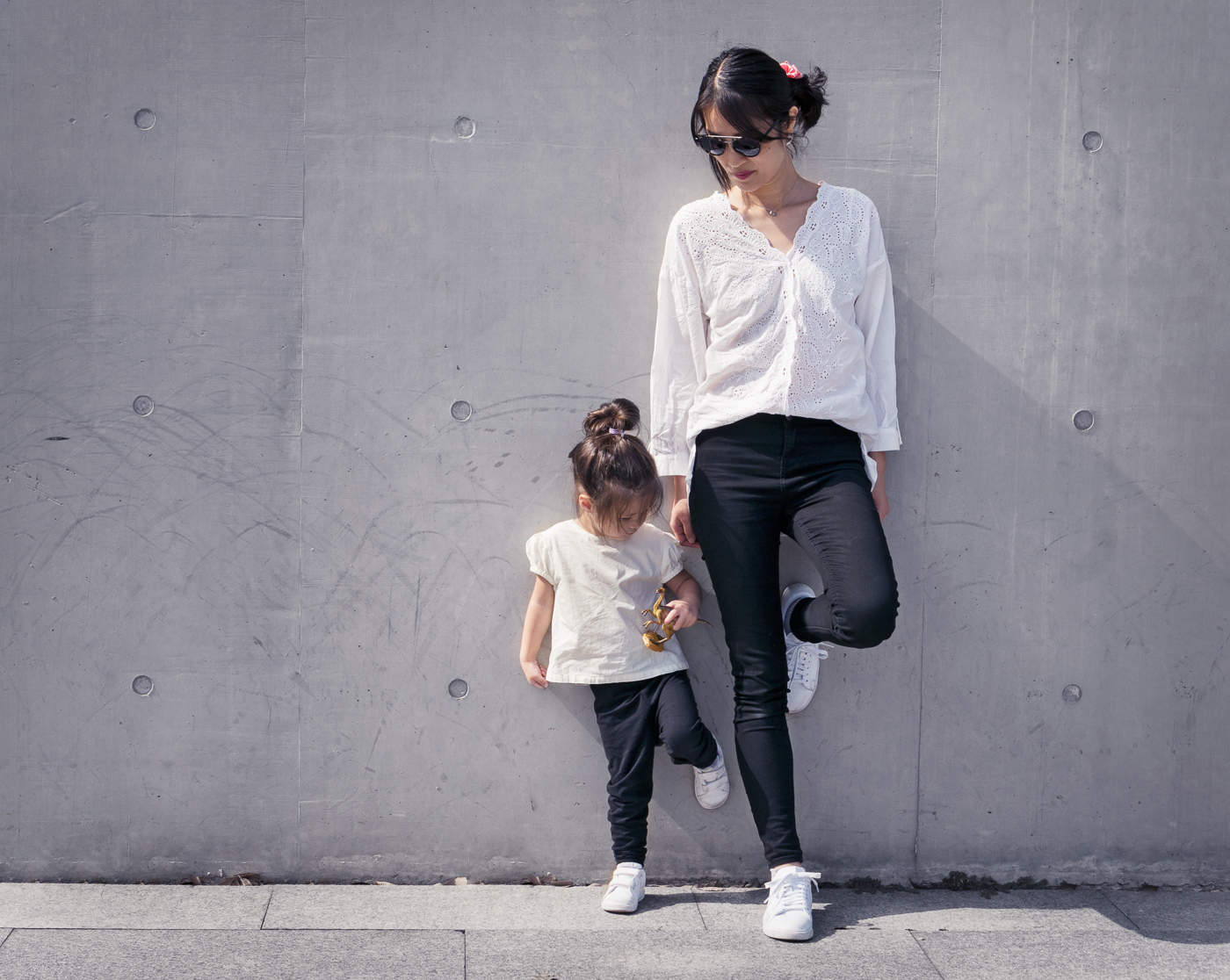 The bright sunlight and the concrete wall made me think of fashion so I asked my wife to pose and of course our daughter copied her.