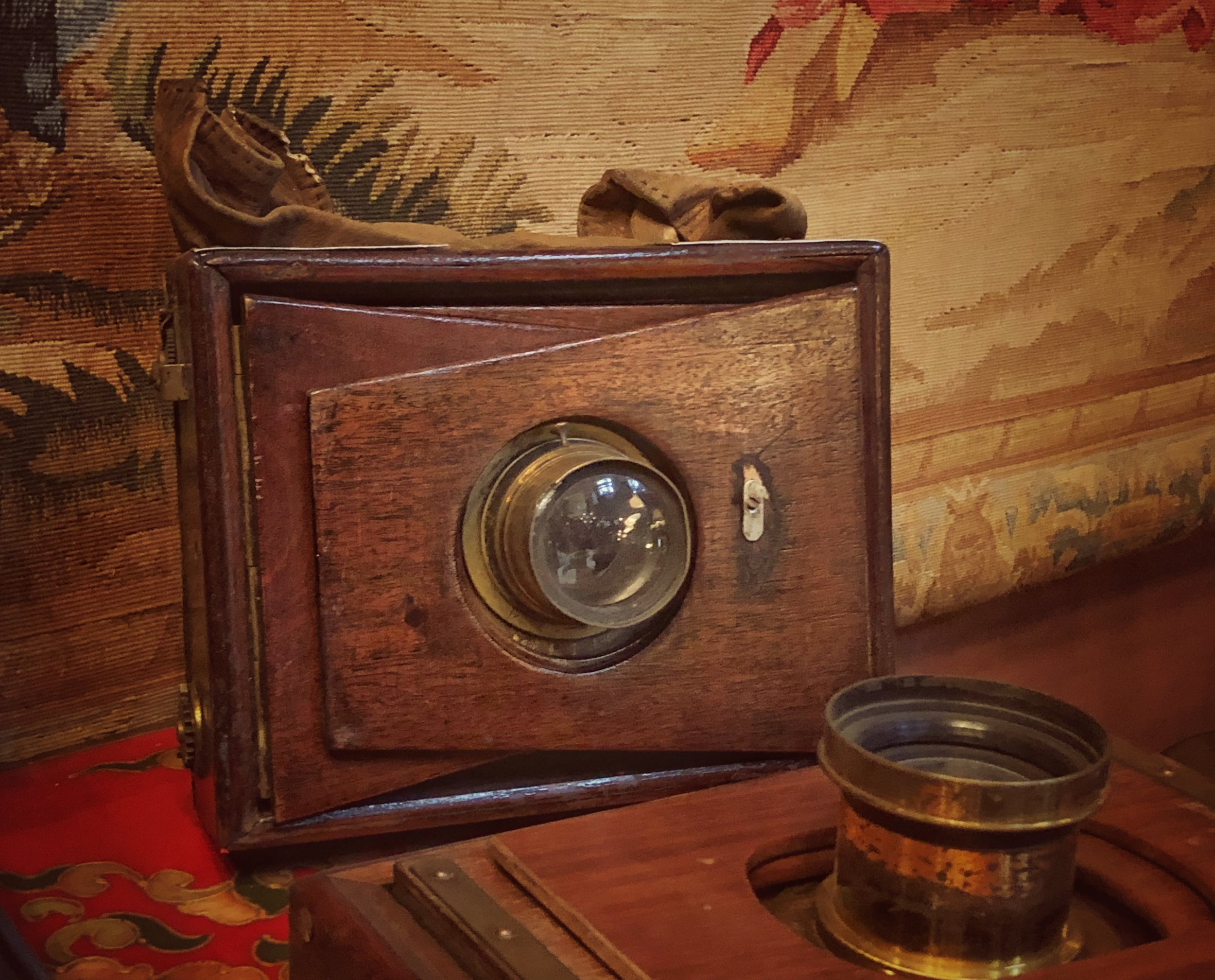 A wooden box large format camera with brass lens.