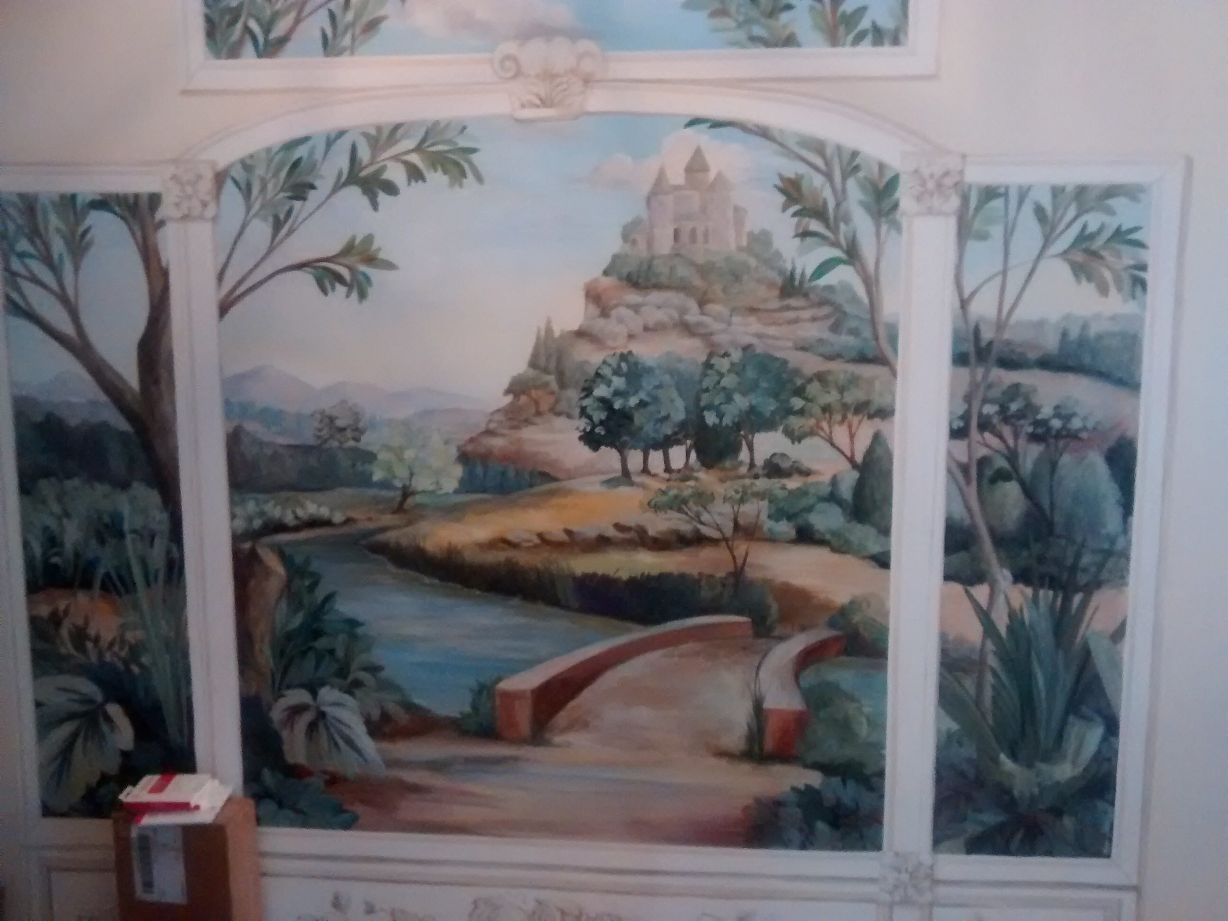 "This Foyer mural is created to fool the eye. The French call it Trompe L'oeil, translated to mean ""fool the eye"". When designing this mural, it was important to create the illusion of open air and space in an area that wasn't able to accommodate furniture or accessories to give it space or personality.  A traditional landscape was chosen for it's timeless beauty.  There are nice accents and details for your eyes to rest upon.  It could be raining to dangerous flood levels or snowing enough to shut down a city, but will always be a beautiful day in your foyer with this mural."