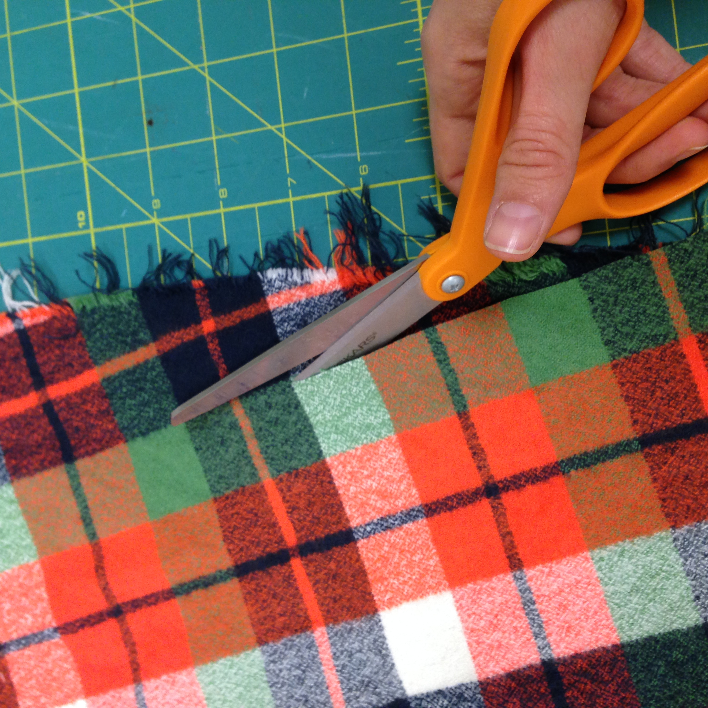 Cutting along the edge of the green stripe of the fabric to find the grain.