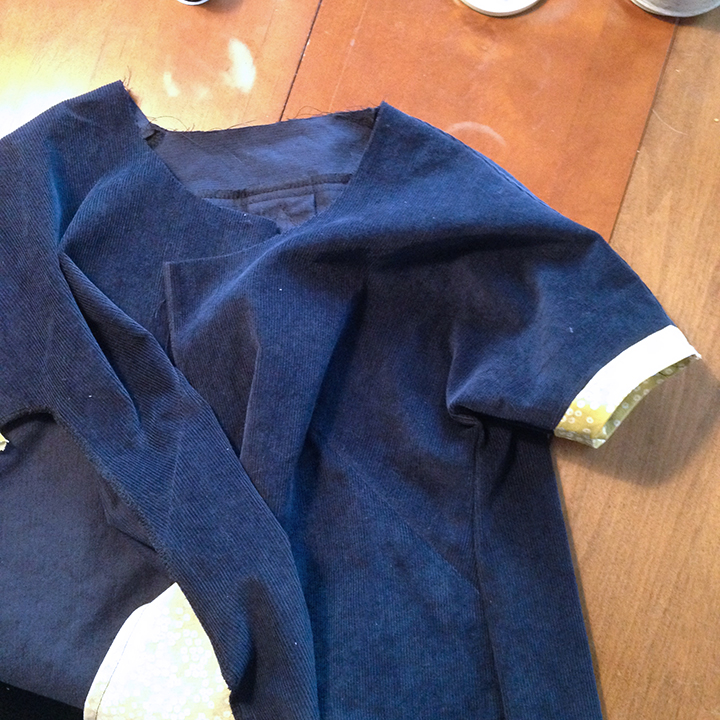 Shoulder seams and one side seam sewn and bias tape is attached to the sleeves.