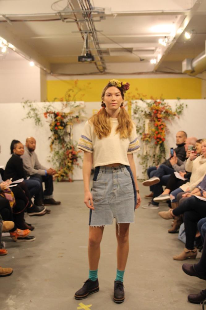 Viviann wears a mock neck sweatshirt tee with 'rag rug' sleeves. Her skirt is by Nathalia Jmag and her bracelet is by Peston.