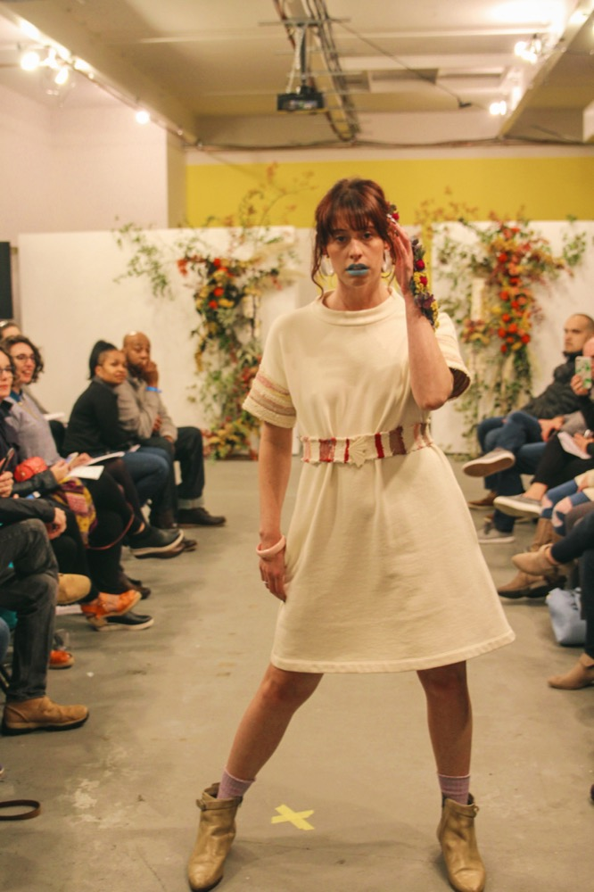 Christa wears a terry mock neck dress with 'rag rug' sleeves and matching handwoven belt fastened with a vintage brooch.