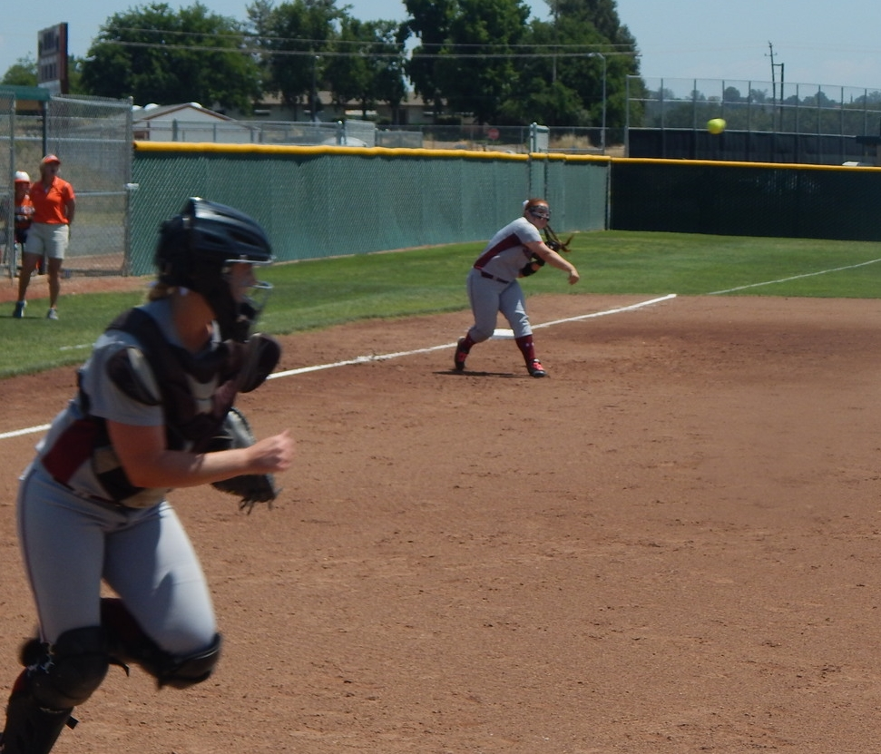 Sierra's Kaitlyn Garcia (far) throws to first.  Syndi Scott (near) runs towards first base.  ( Jeremy McDonald-65 Sports)