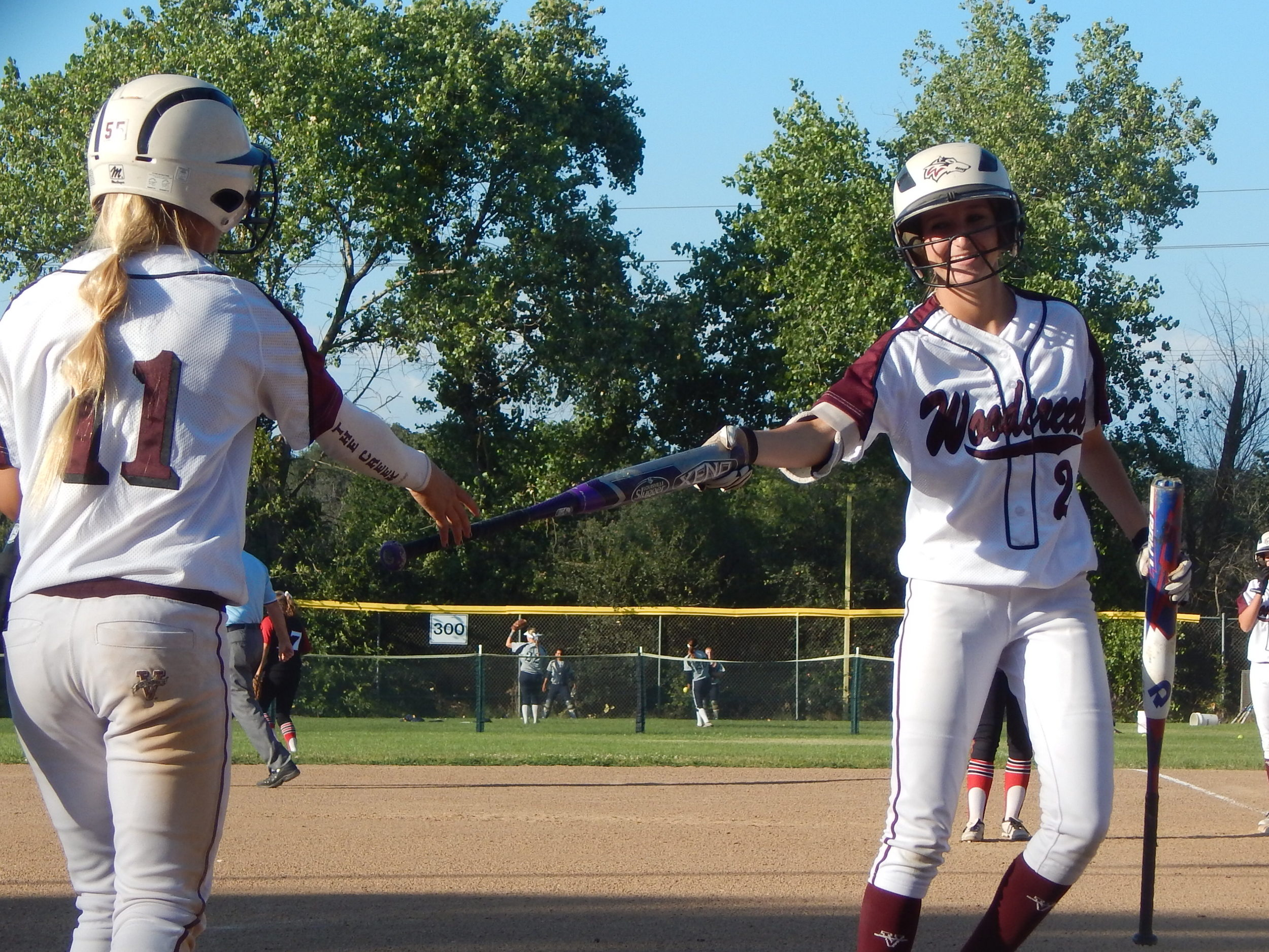 Woodcreek's Rebecca Bernard hands Caity Szczesny the bat following an at-bat.  ( Jeremy McDonald 65 Sports)