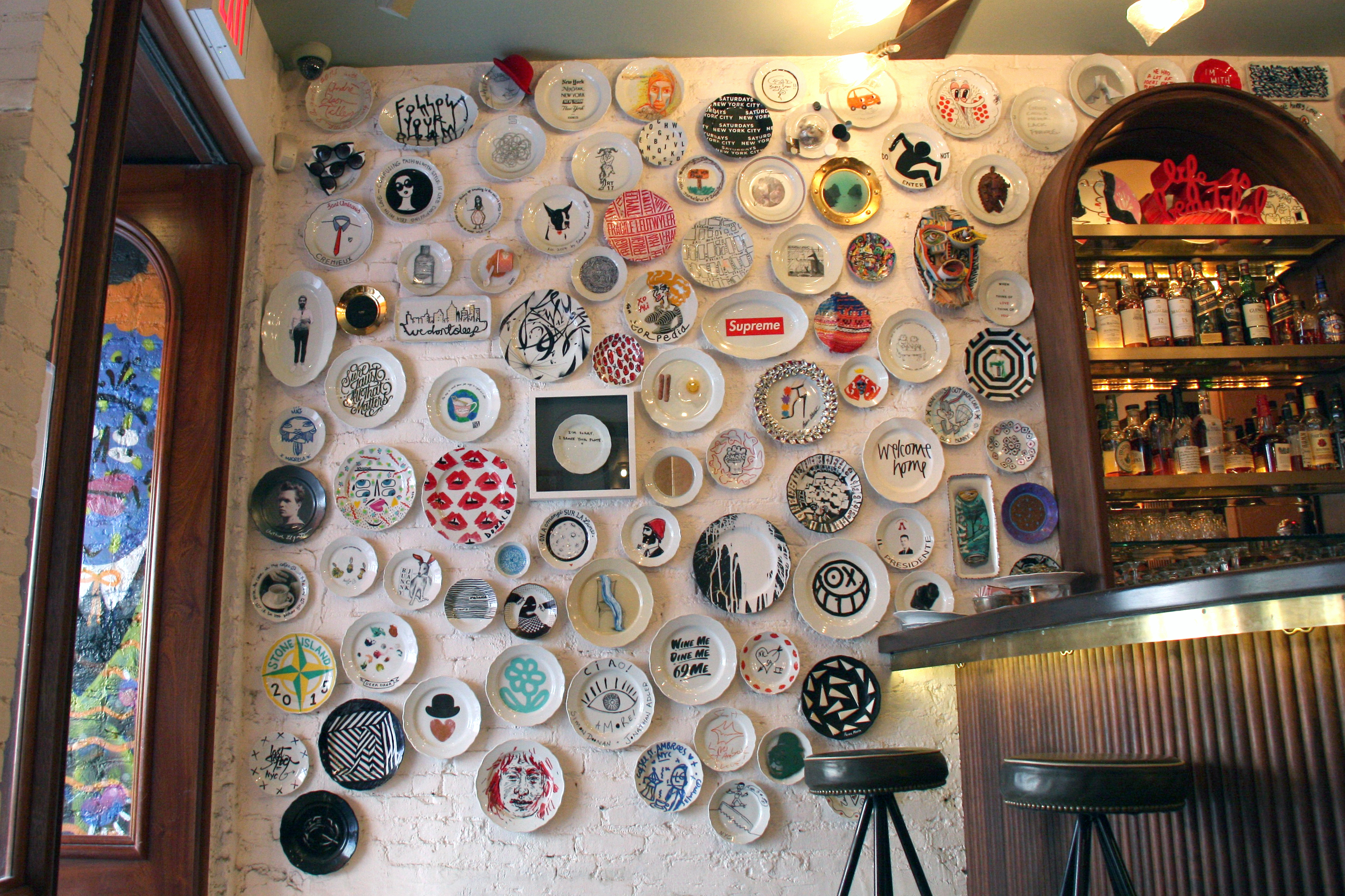The famous plate wall at Sant Ambroeus Soho. Photo courtesy of Sant Ambroeus.