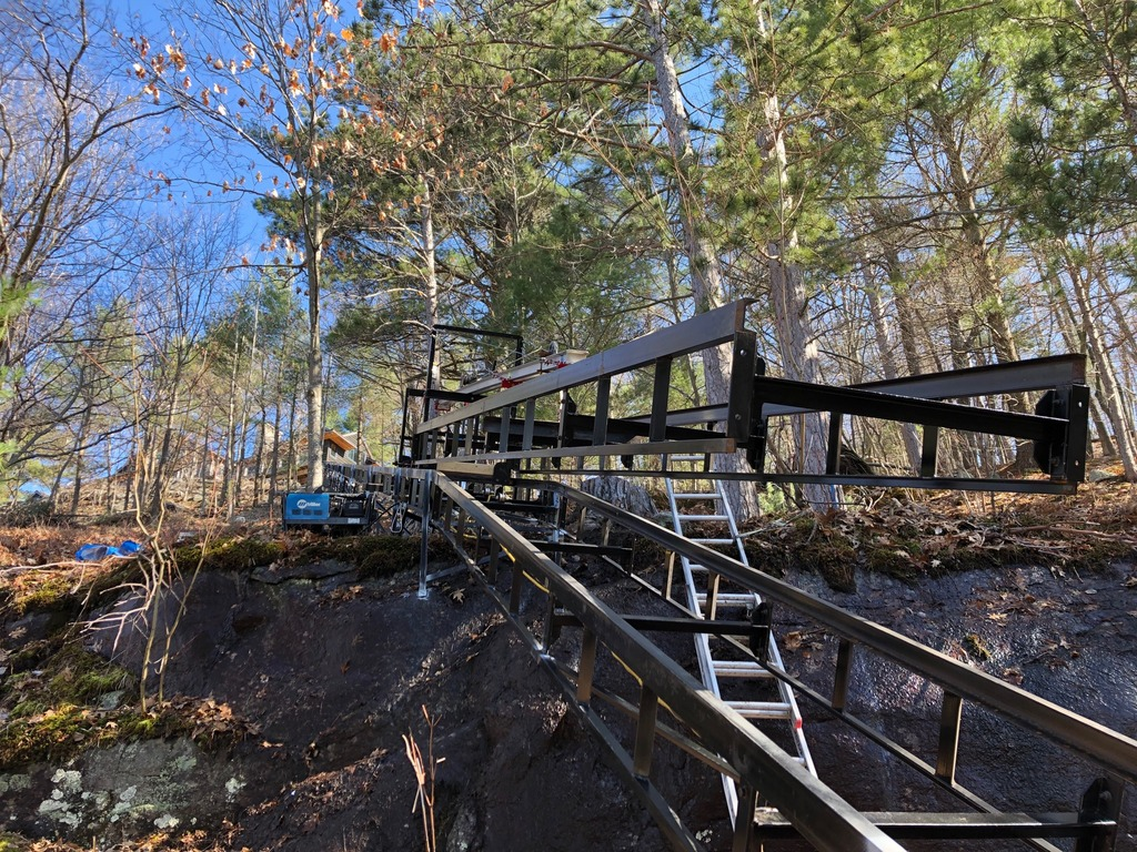 Looking up the track at the finished top curve and 200' on to the cottage. The installation hoist is carrying a 20' section of track to the third pitch. This change in angle is small in degrees but pretty obvious at 20'.