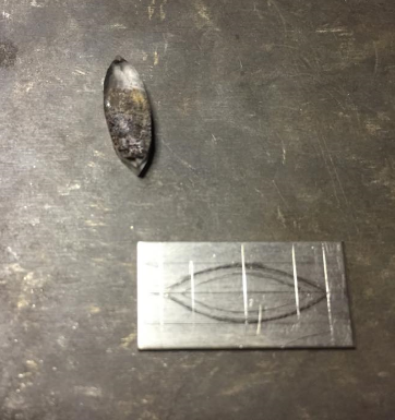 Tracing the base ofthe setting onto 14k white gold sheet before cutting out.