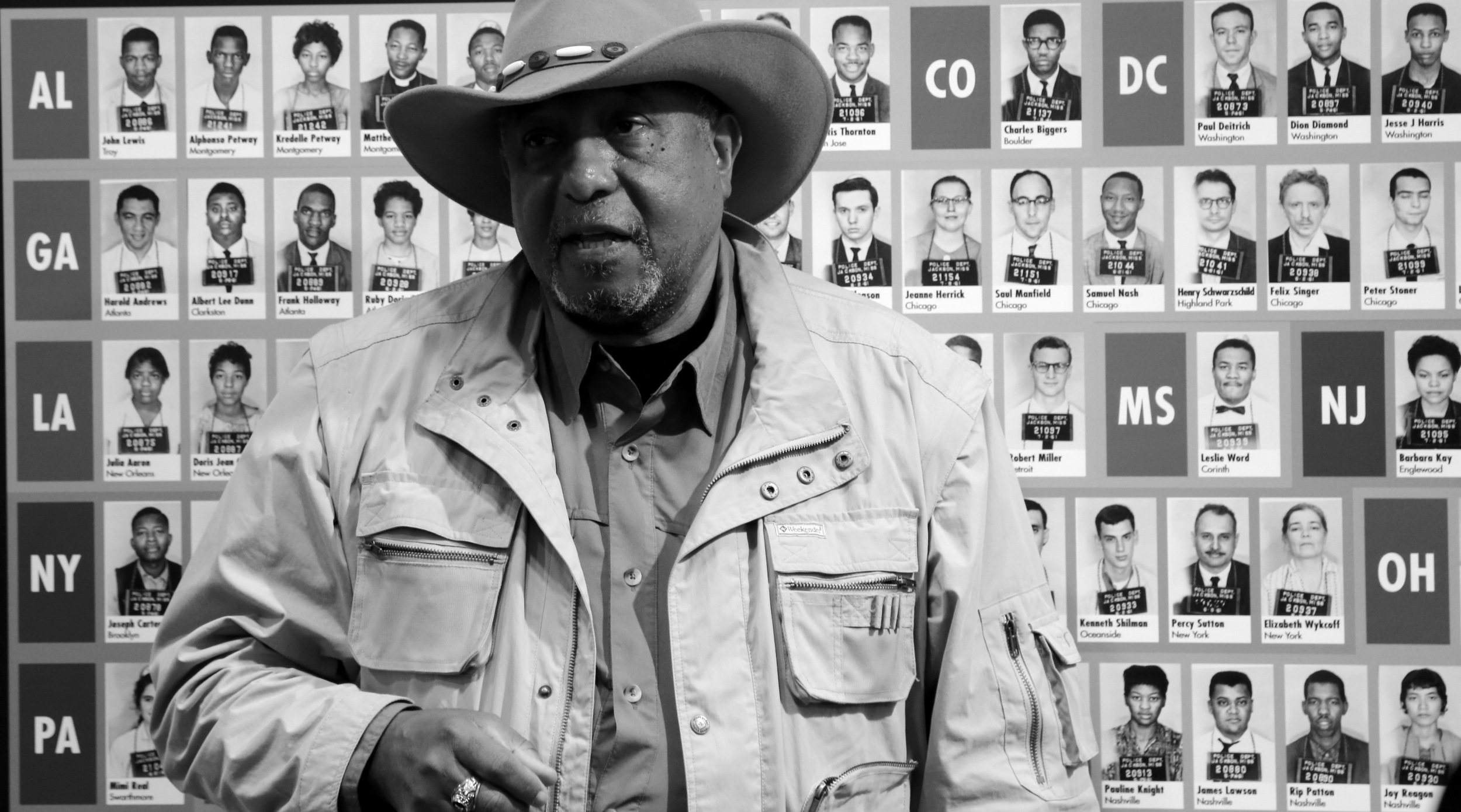 Bernard Lafayette in front of the wall of mugshots of the Freedom Riders at the Freedom Ride Museum  photo by Troy Bonnes