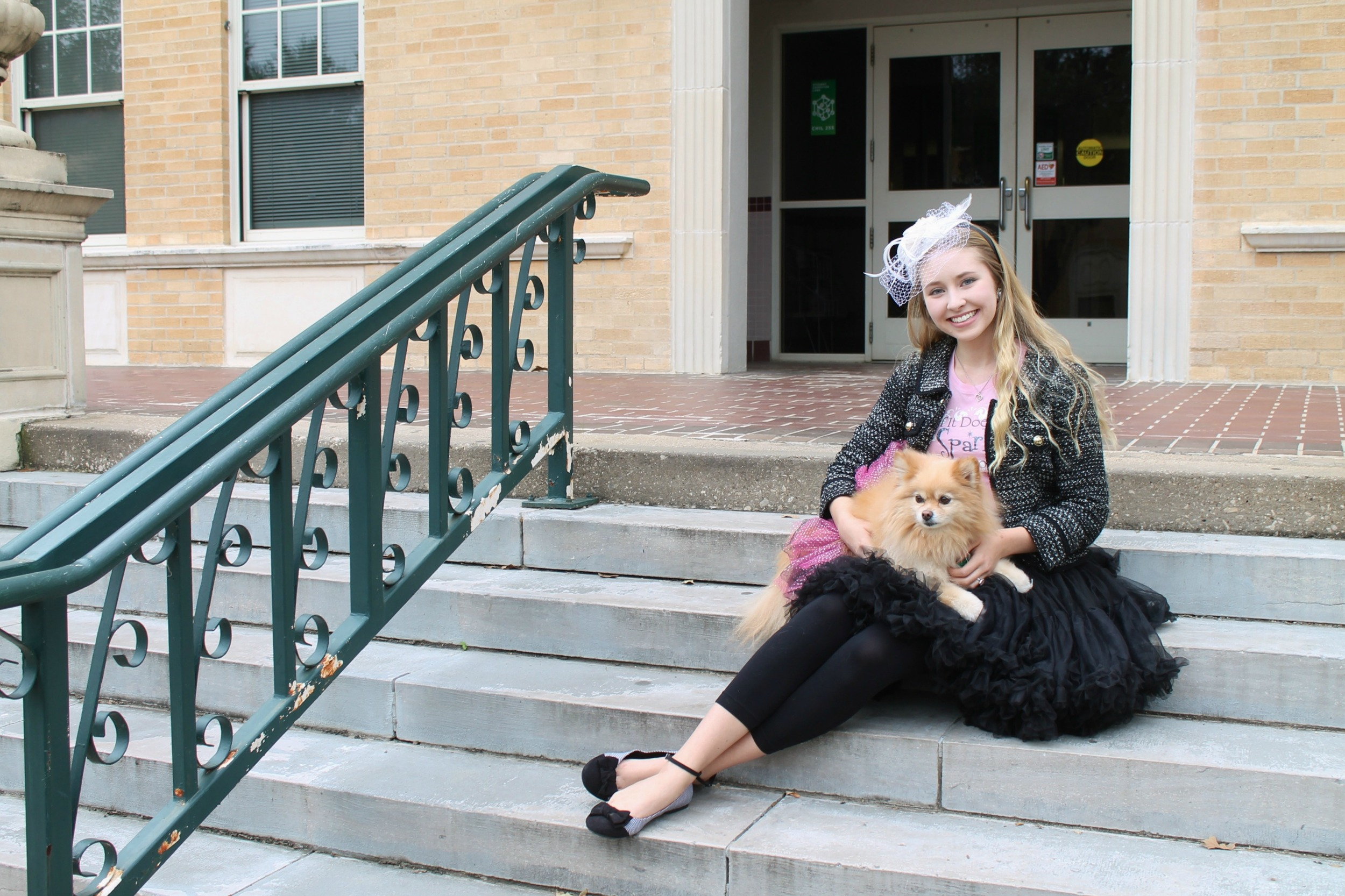Delaney poses on the steps of Chilton Hall with her dog, Paris.