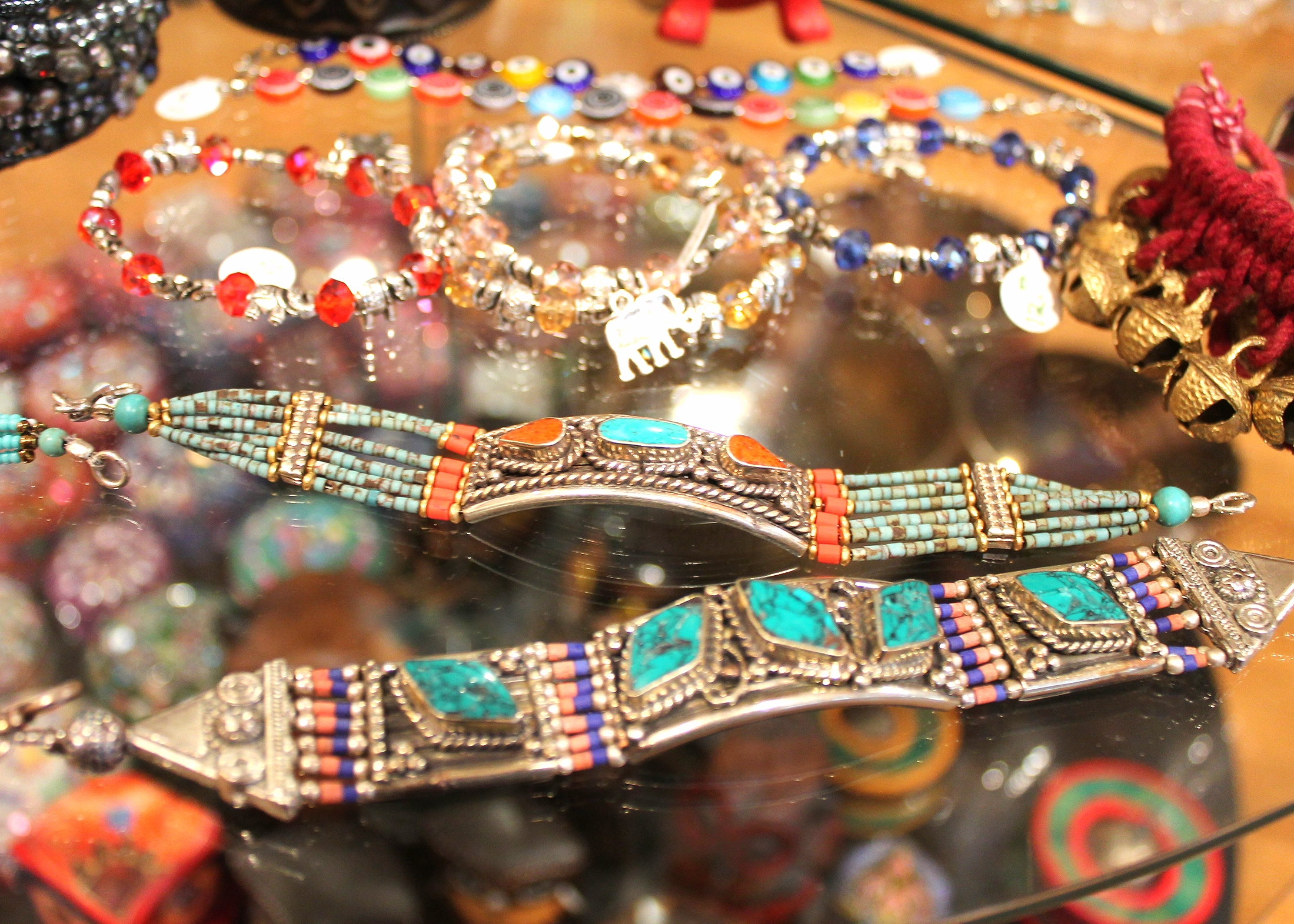A small selection of bracelets the store offers. The front metal bracelets are crafted in a Nepali style from real turquoise, coral, and lapis lazuli.