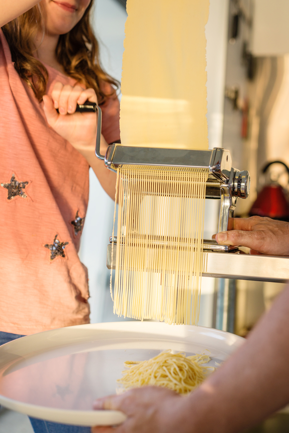 Cutting pasta photo from Stocksy