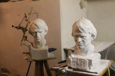 The nearly completed portrait bust in marble, alongside the plaster cast from which it was copied.