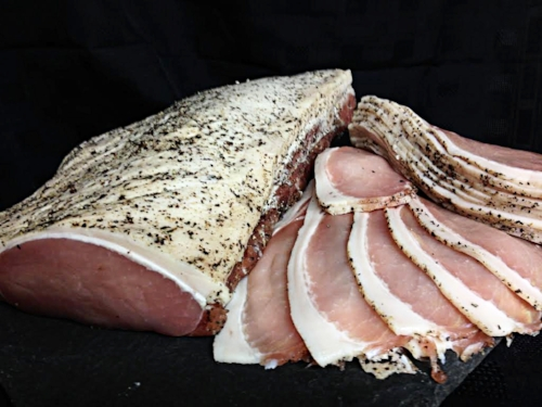 Free range plain back bacon which has been dry cured with juniper and black pepper.