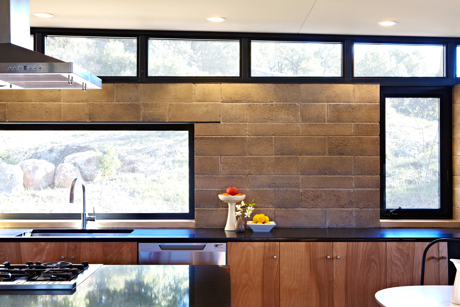 Bronze anodized window frames, black Cesarstone contertops, natural birch cabinets and Watershed Blocks. Lighted from above as they are here, the color variations in each individual block reveal the minerality of their composition. Find out more at the   Watershed Materials  website.
