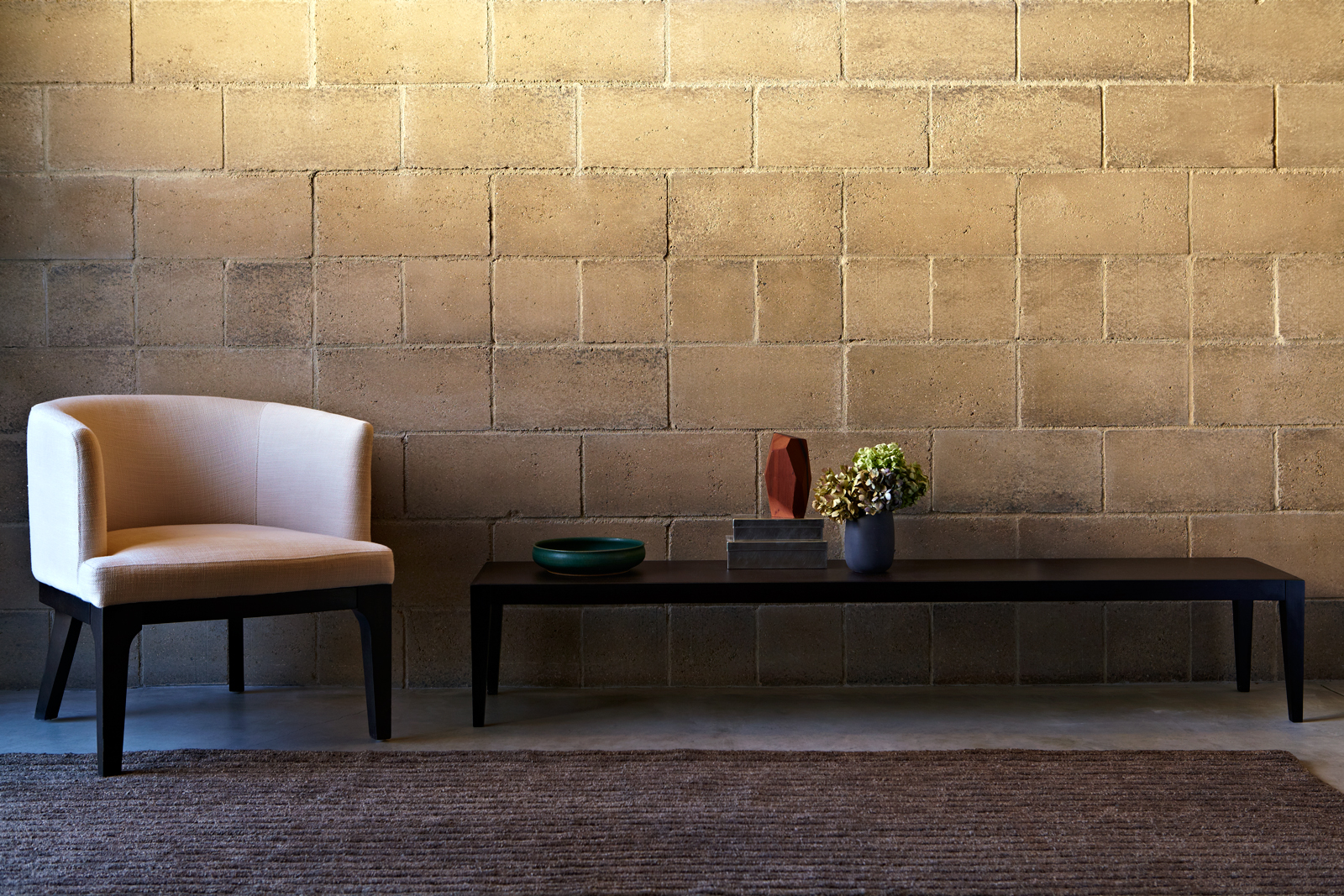 A soldier course of eight inch blocks with a white linen club chair and hand woven Odegard rug. Just as natural rock is made up of a million individual grains of quartz, feldspar, and trace elements, Watershed Blocks celebrate their unique composition. Unlike uniform concrete blocks, made of cement and dye, no two Watershed Blocks are exactly the same. Find out more at the  Watershed Materials  website.