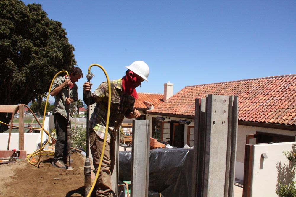 Rammers have reached the top of the rammed earth wall that surrounds the now buried eucalyptus branches.