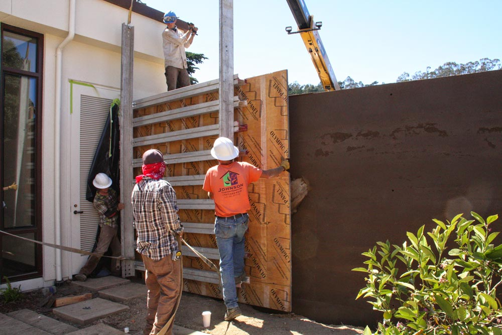 Formwork is removed revealing a freshly packed rammed earth wall and the center point of the ball of gnarled eucalyptus branches. Both the raw earth for the rammed earth wall and the eucalyptus wood was sourced from the surrounding Presidio.