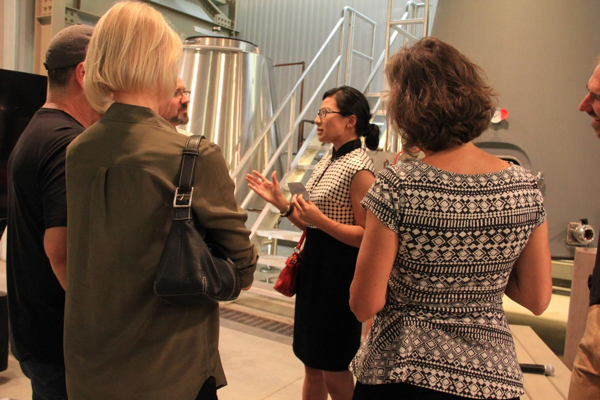 Dr. Rongrong Hu speaking with attendees of her presentation asking them their feelings on the future of rammed earth.