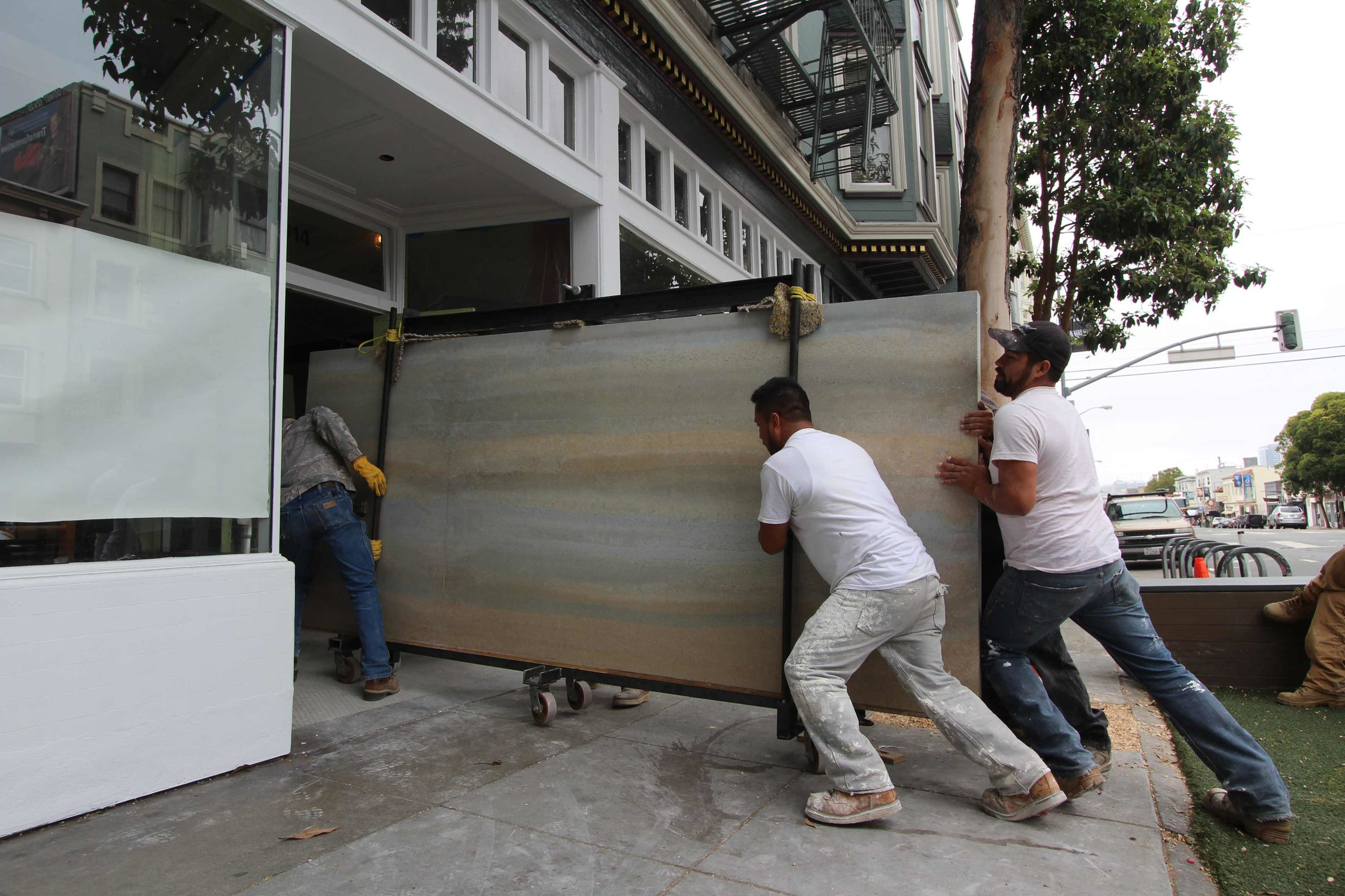 Pre-cast interior rammed earth panels being delivered to the new Reformation store in the Mission district of San Francisco. To accomplish the delivery - which had to be made through the storefront's narrow front door with no room for a forklift or crane - we built a portable jib to transfer each 2,000 pound panel from the trailer to the sidewalk and we built a six-wheeled trolley to roll the panels into the store. As you can see, it took three people pushing and one pulling to get the panel up and over the door threshold. The rammed earth arrived safe and ready for installation in a retail store that could have never used the material with traditional on-site form setting methods.