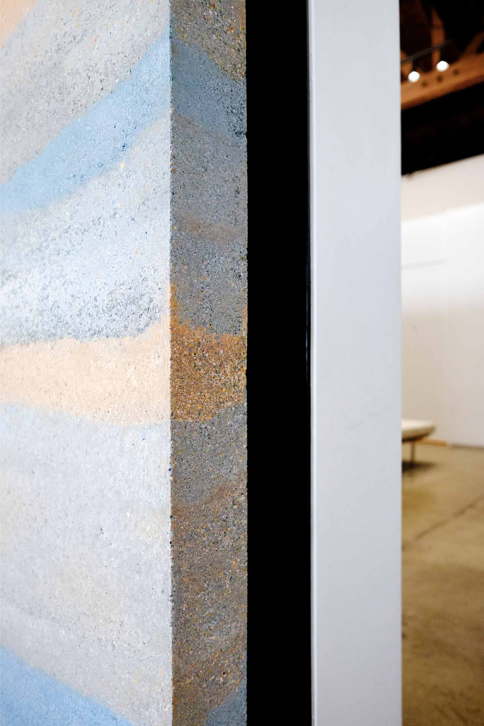 """Pre-cast thin interior rammed earth panel at the Reformation store in Los Angeles. After curing in the shop for a month, each of the panels was cut in half to facilitate transport, then re-assembled in the store and mounted onto a square tube steel frame bolted to footings beneath the original concrete slab floor. The """"end grain"""" of the cut panels reveals the small stones and gravel that are a component of the formulations that give each layer its strength and color. Image © Jesse Gillan"""