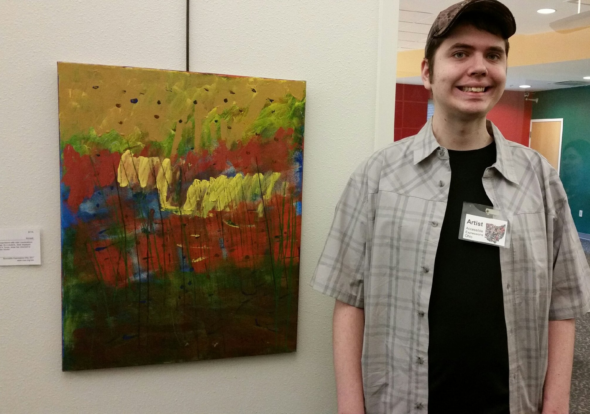Artist Jesse Fields giving a brilliant smile next to his acrylic painting. Proud moment for friends and family at the art show!