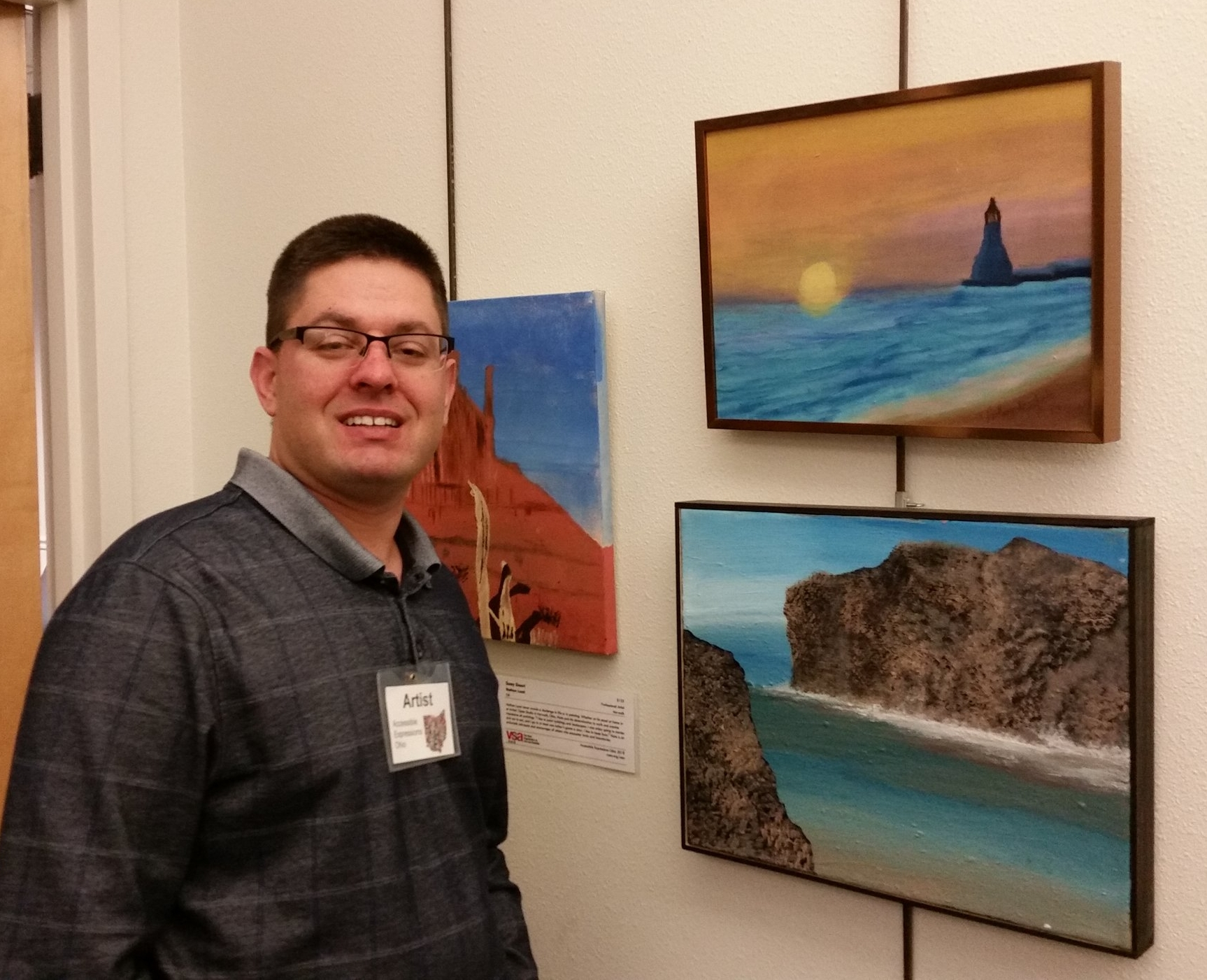 "Tony with his beautiful oil painting ""Elbert Beach"" (top right)     Nathan Lucal's painting ""Sunny Dessert"" is behind Tony"
