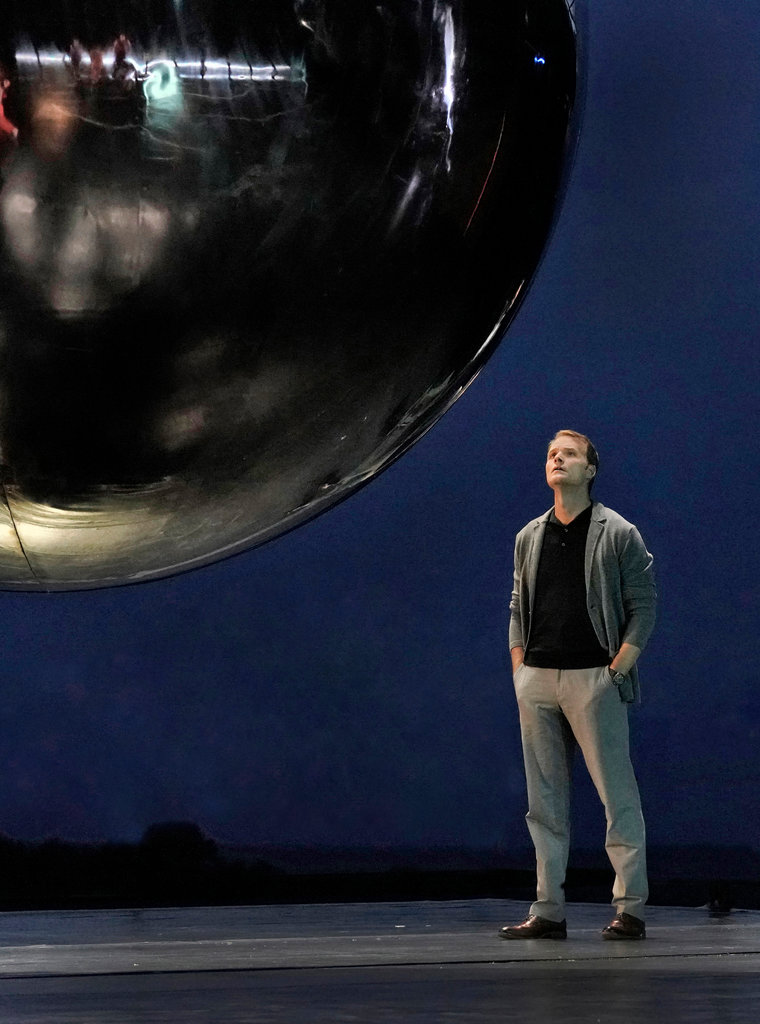 "Ryan McKinny as J. Robert Oppenheimer in ""Doctor Atomic"" at Santa Fe Opera, with a gigantic sphere representing nuclear weapons and the desert visible beyond the stage.                                                                    Ken Howard for Santa Fe Opera"