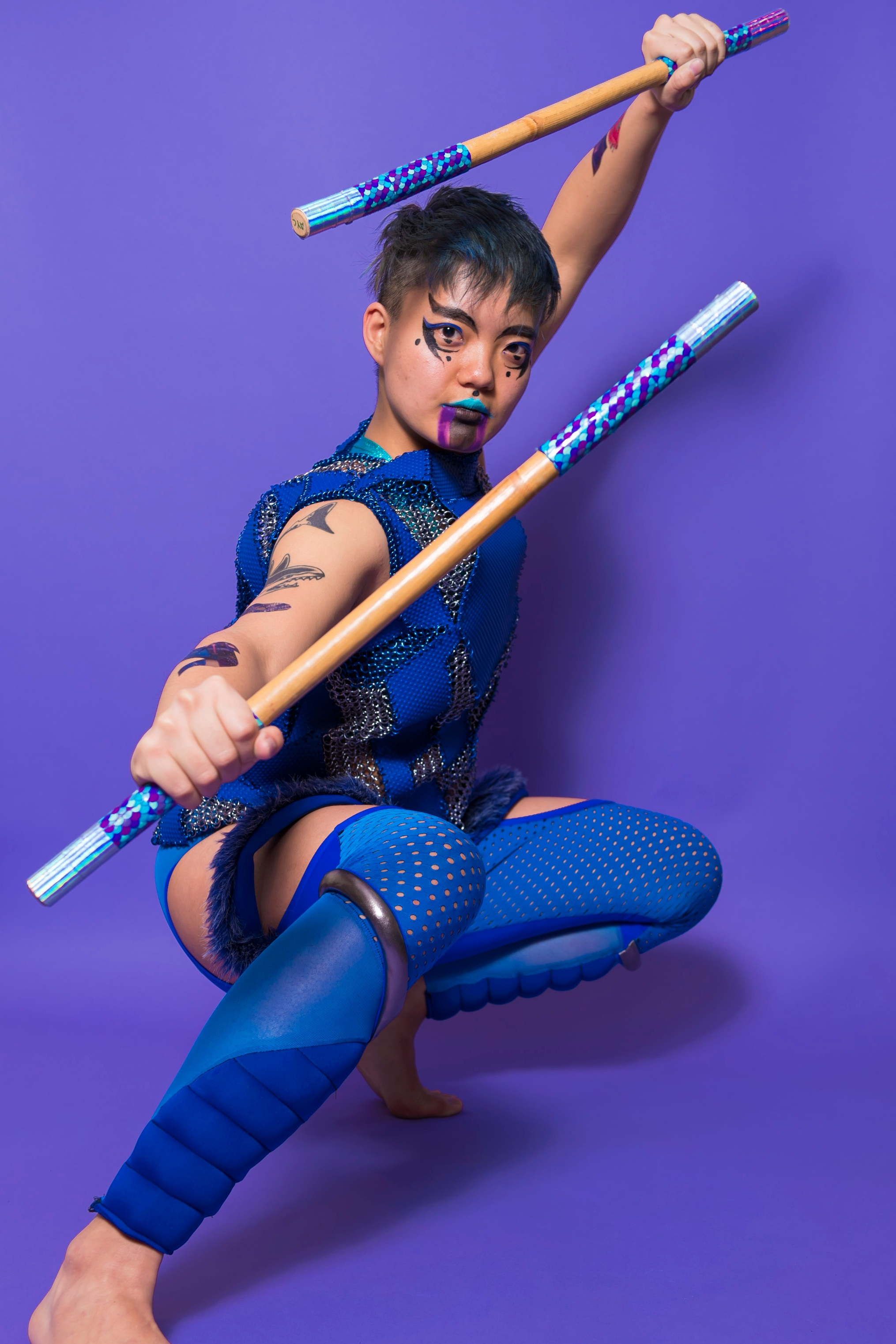 Image description: photo of me crouching in a fighting distance and holding my Eskrima sticks above my head defensively against a purple background. I'm wearing a blue vinyl and chainmaille vest inspired by traditional Filipino armor, and blue leggings with thigh cut-outs, silver trim, and furry dangly straps. I have curly and pointy makeup in purple, blue, and black on my face and arms. Outfit by Radical Visibility Collective. Makeup by Jerico Domingo. Photo by Colectivo Multipolar. Performance at Chicago History Museum, March 2018.