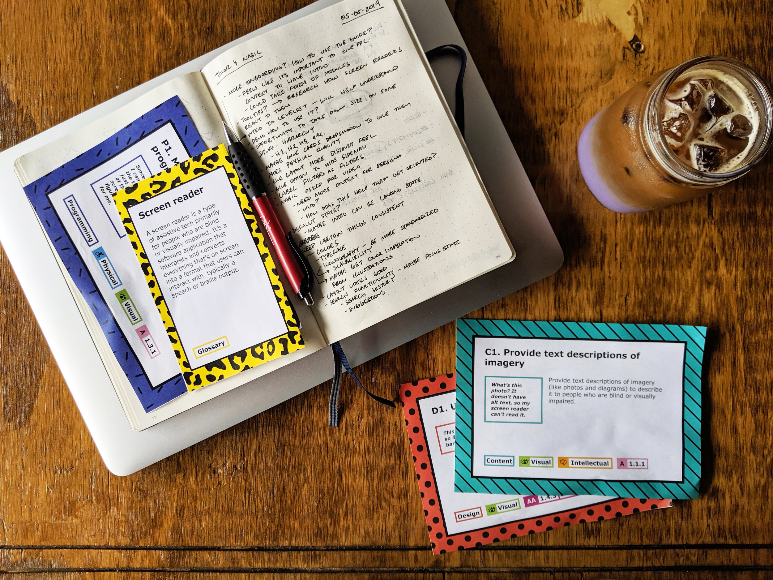 Image description: photo from above of colorful yellow, purple, turquoise, and red-orange cards, my open sketchbook with handwritten notes, my closed laptop, and an ube latte drink all on a hardwood desk surface. Photo taken at First Sip Cafe in Argyle.