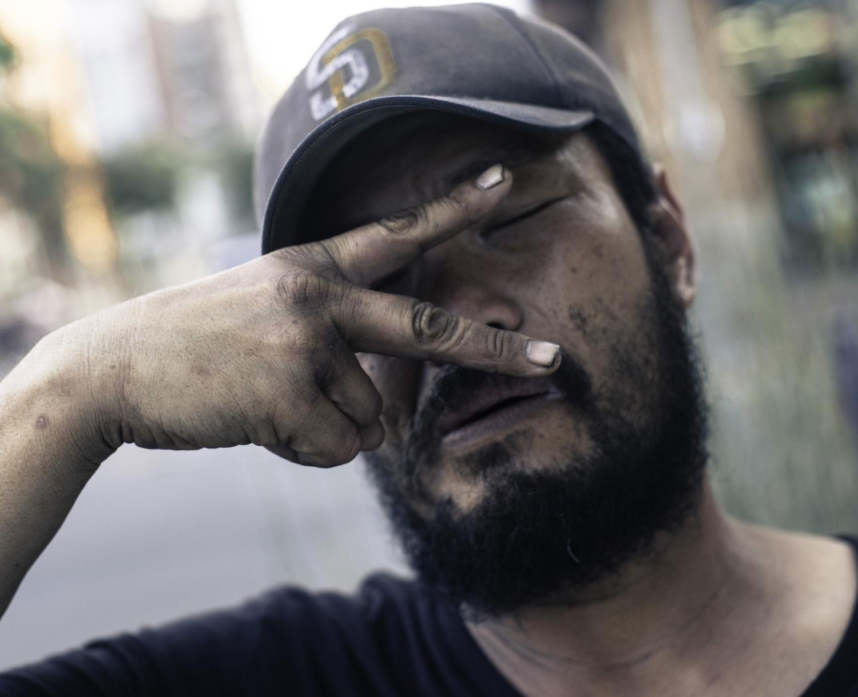 Asian homeless fingers over eyes.jpg