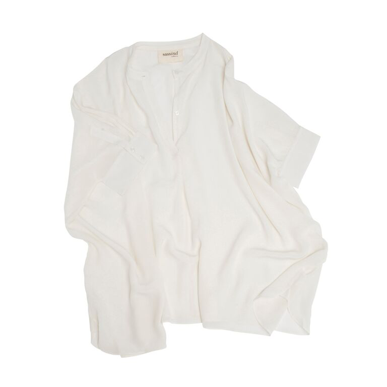 100% Silk Freestyle Blouse In Off White     Relaxed fit short sleeve blouse. Pair with denim jeans for classic day wear, or pair with our charcoal merino leggings, gold leather ballet slipper, and some simple jewellery for a classic evening wear outfit. Looks just as great a little crinkled as it does wrinkle free. It also works beautifully under our merino oversized wrap. Simple. Classic. Elegant.