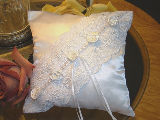 Rose Bouquette  This ring bearer pillow has romance written all over it. White scalloped lace with rose border draped over white satin, ornamented with lily lace ribbon and topped off with satin roses. The narrow ribbon attached in center will hold your rings and the band on back will allow for easy handling during the ceremony. Measures approx. 8 x 8 inches