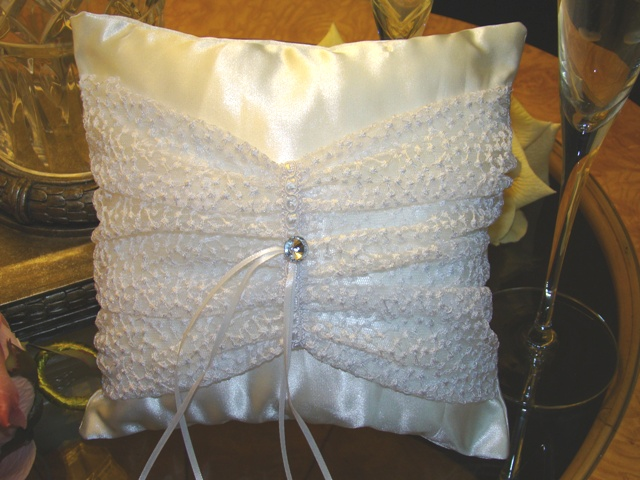 "White Illusions  White dotted tulle gathered and held together with lace ribbon in center and enhanced with large crystal button. A set of narrow ribbons will hold your rings and thehand ribbon on back of pillow will allow easy handling during ceremony. Measures approx. 8"" x 8"""