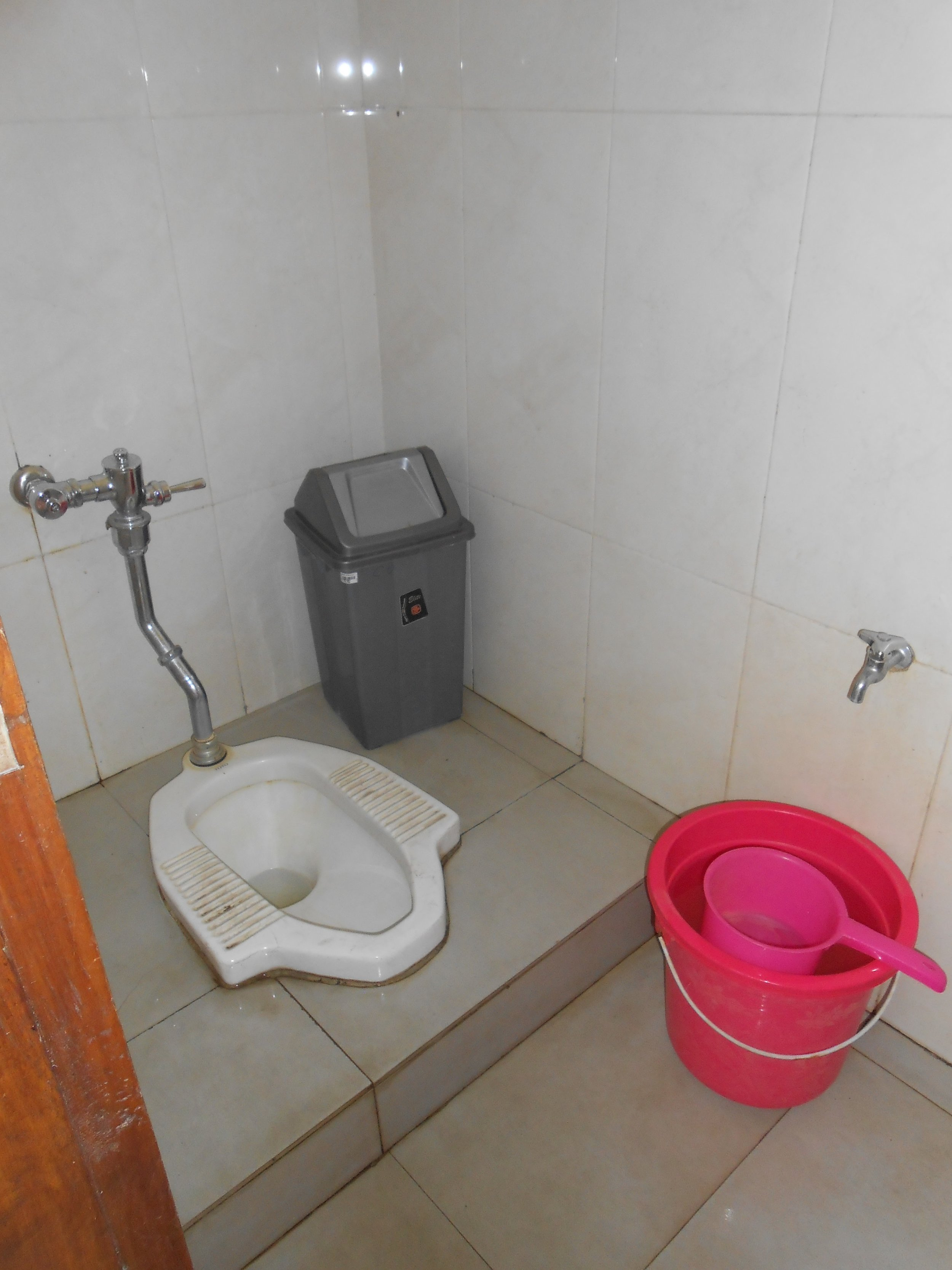 Indonesia squat toilet with water bucket