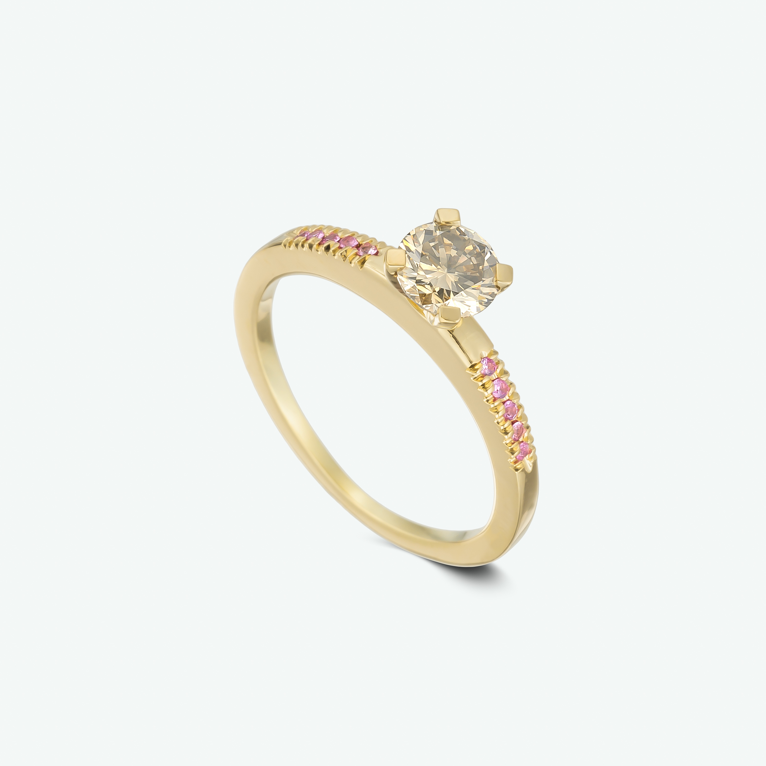One of a kind and unique 14k yellow gold engagement ring set with a stunning champagne diamond and brilliant pink sapphires. CD: 0.60 ct. PS: 0.06 ct.