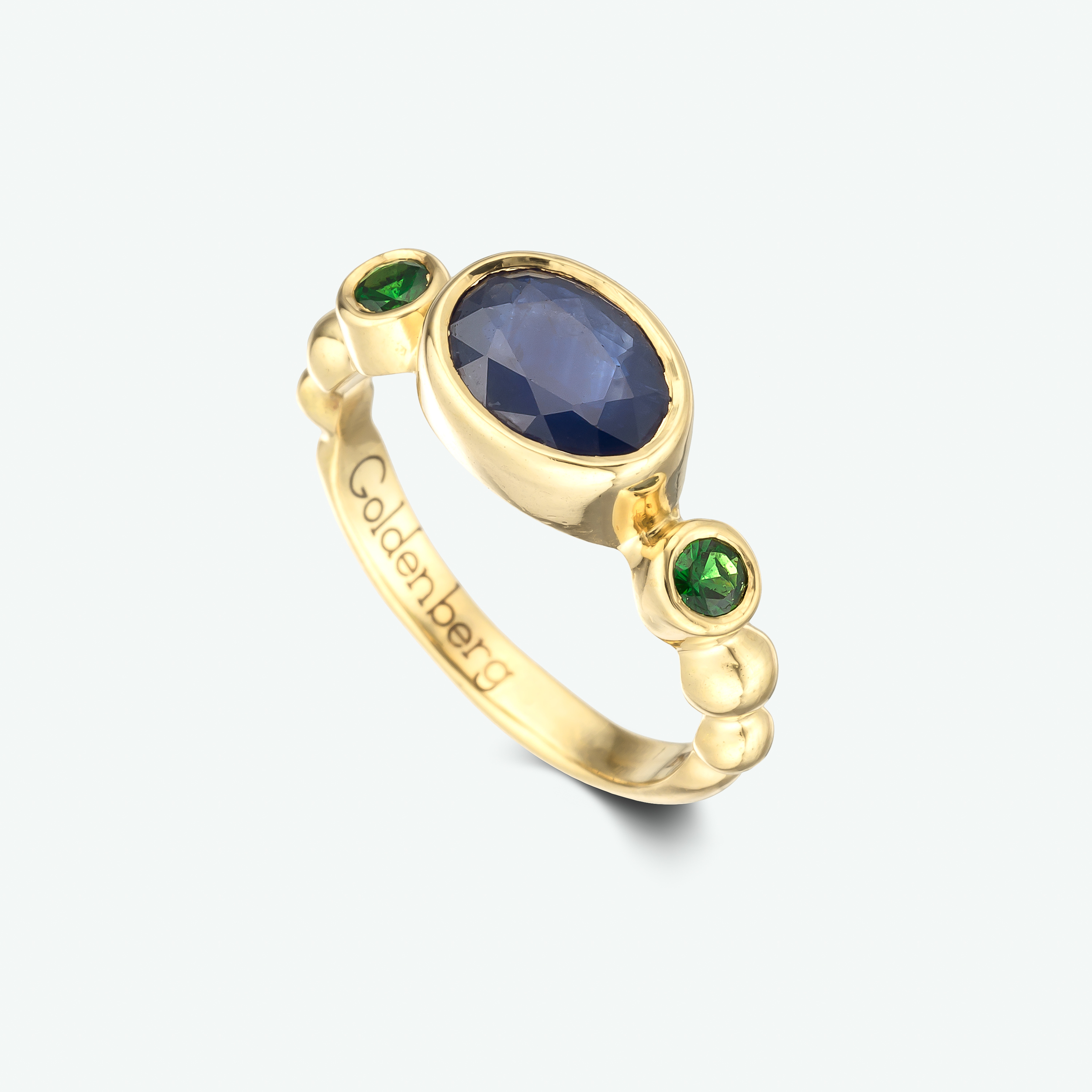 'Family heirloom project' This fabulous ring is composed of 18k yellow gold and set with a lovely dark blue sapphire and green tsavorite garnets.