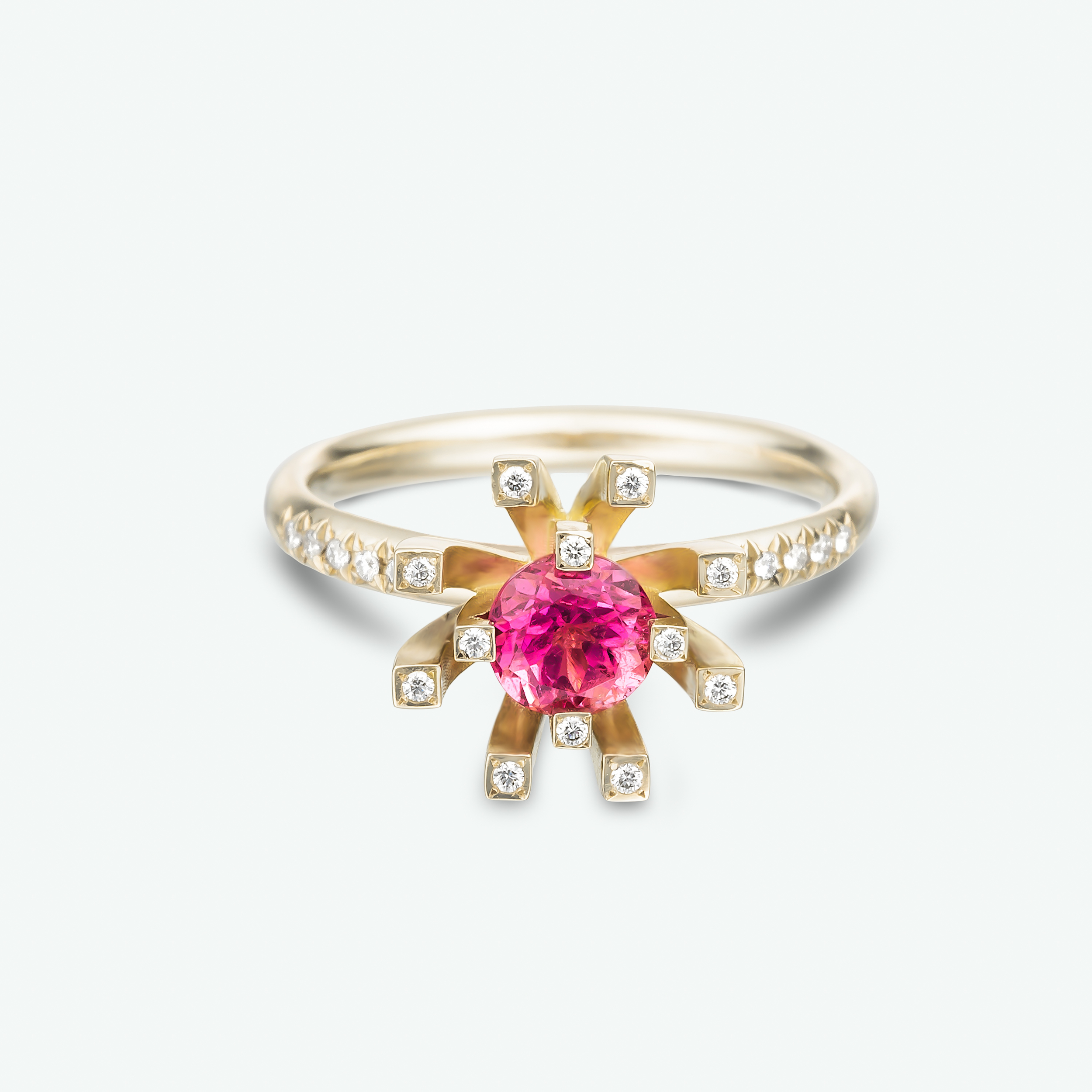 A stunning solitaire pink engagement ring composed of a vivid pink tourmaline and brilliant white diamonds set in a white gold unique diamond halo engagement ring.D: 0.11 ct.     PT: 0.45 ct.
